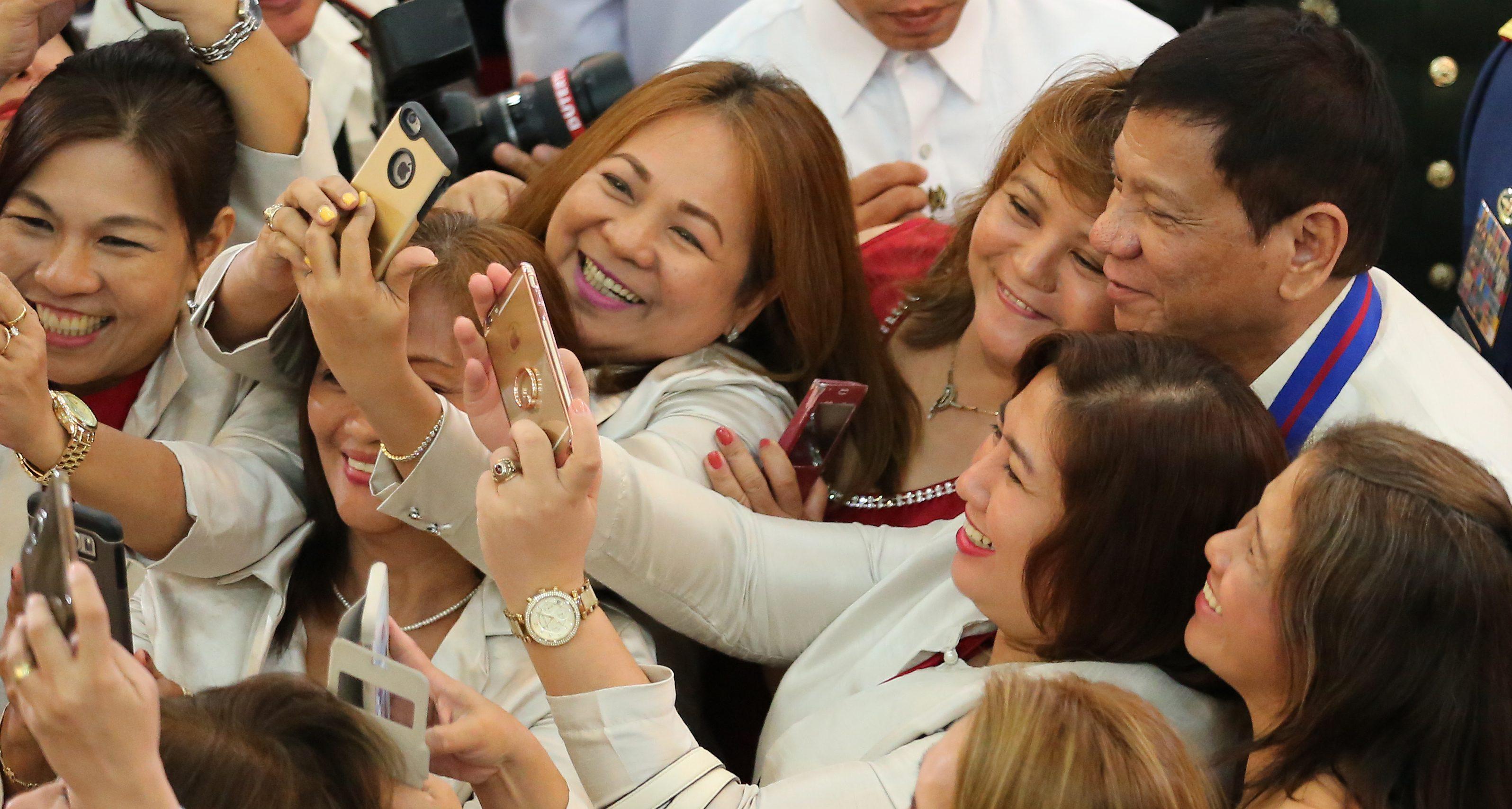 Women take a selfie with Philippine president Rodrigo Duterte in suburban Quezon city, Manila, Philippines, on July 1, 2016.