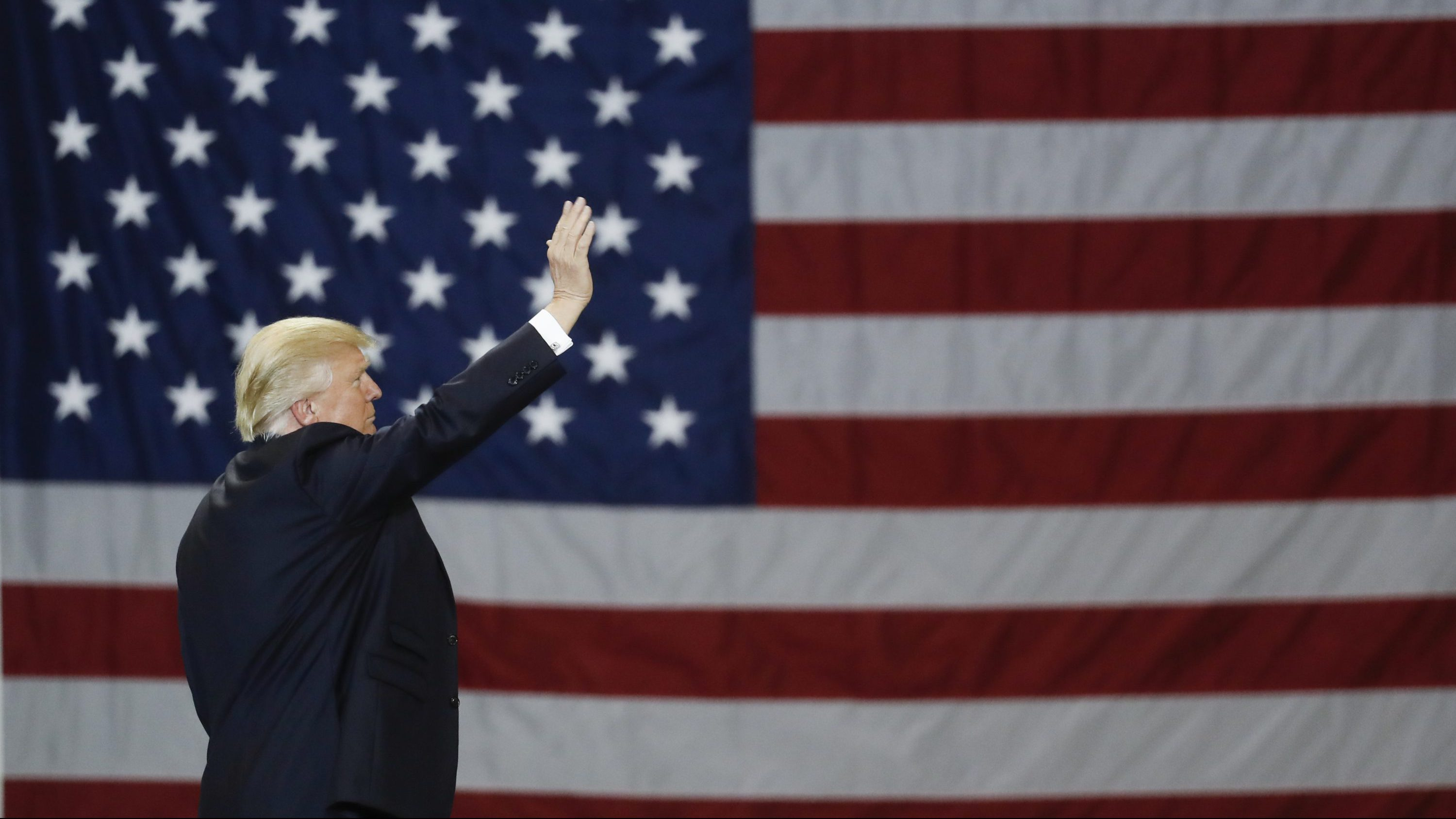 President Donald Trump waves in front of an American flag as he leaves after speaking during a rally at the Kentucky Exposition Center, Monday, March 20, 2017, in Louisville, Ky.