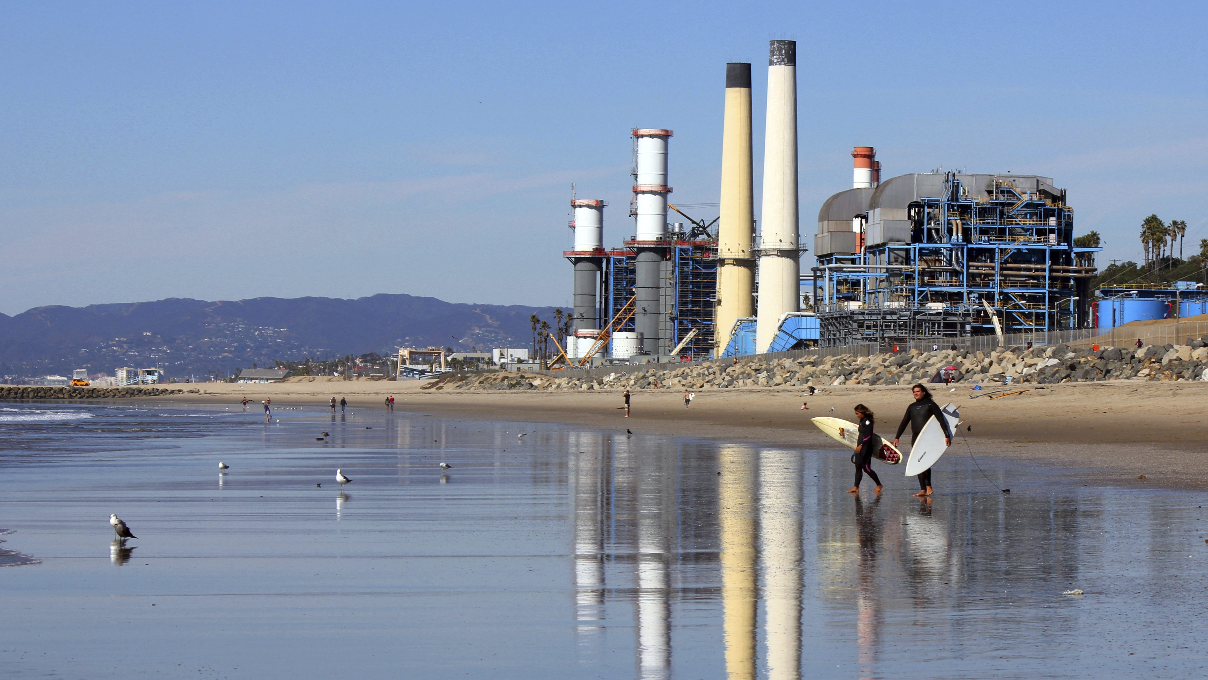 Power plant on a beach in California with surfers in the foreground