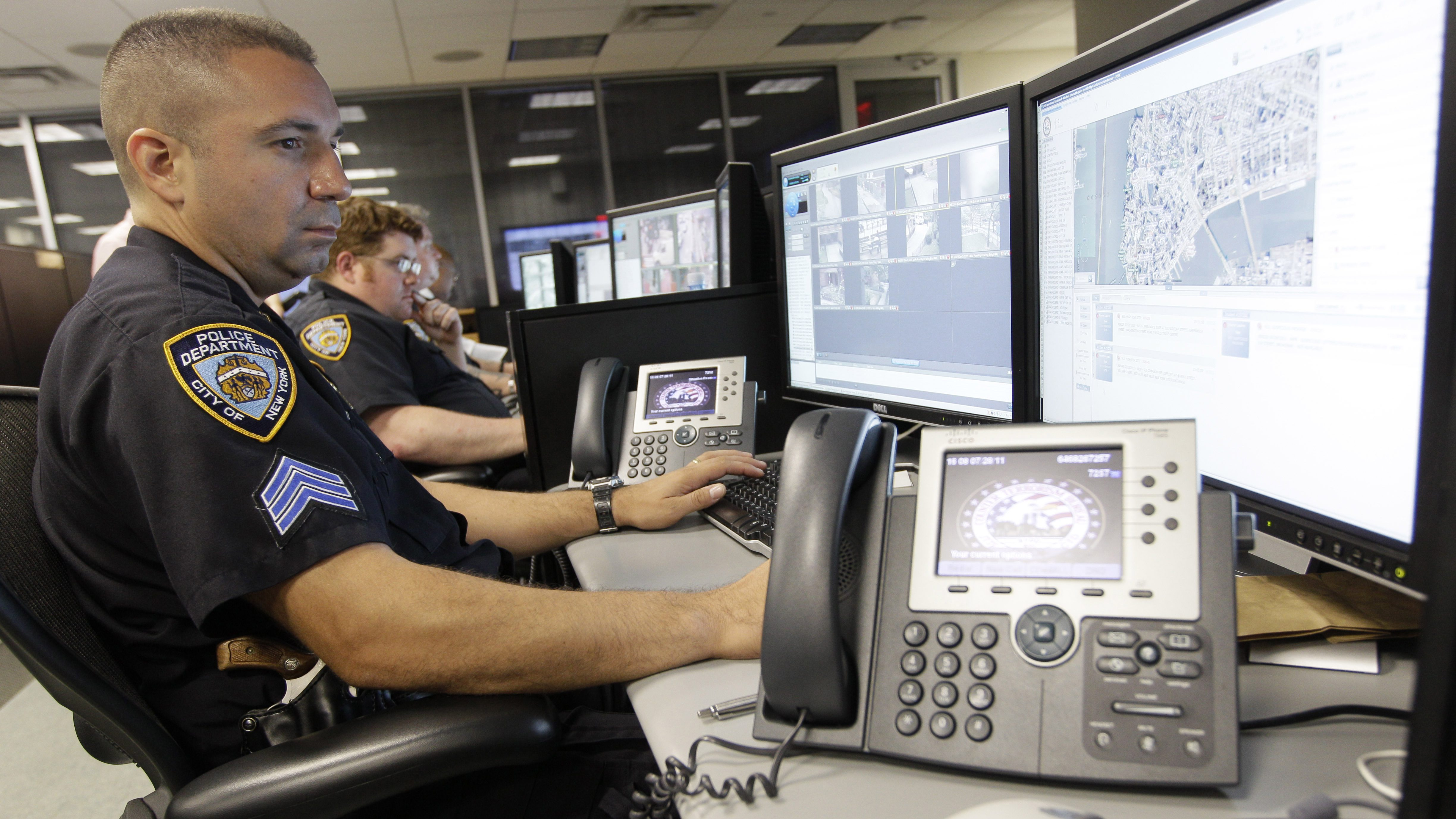 FILE - In this Thursday, July 28, 2011 file photo, police officers look at computer monitors in the operations center of the Lower Manhattan Security Coordination Center in New York. When news came of a terror attack in Paris in early January, the New York Police Department went on high alert. (AP Photo/Mary Altaffer)