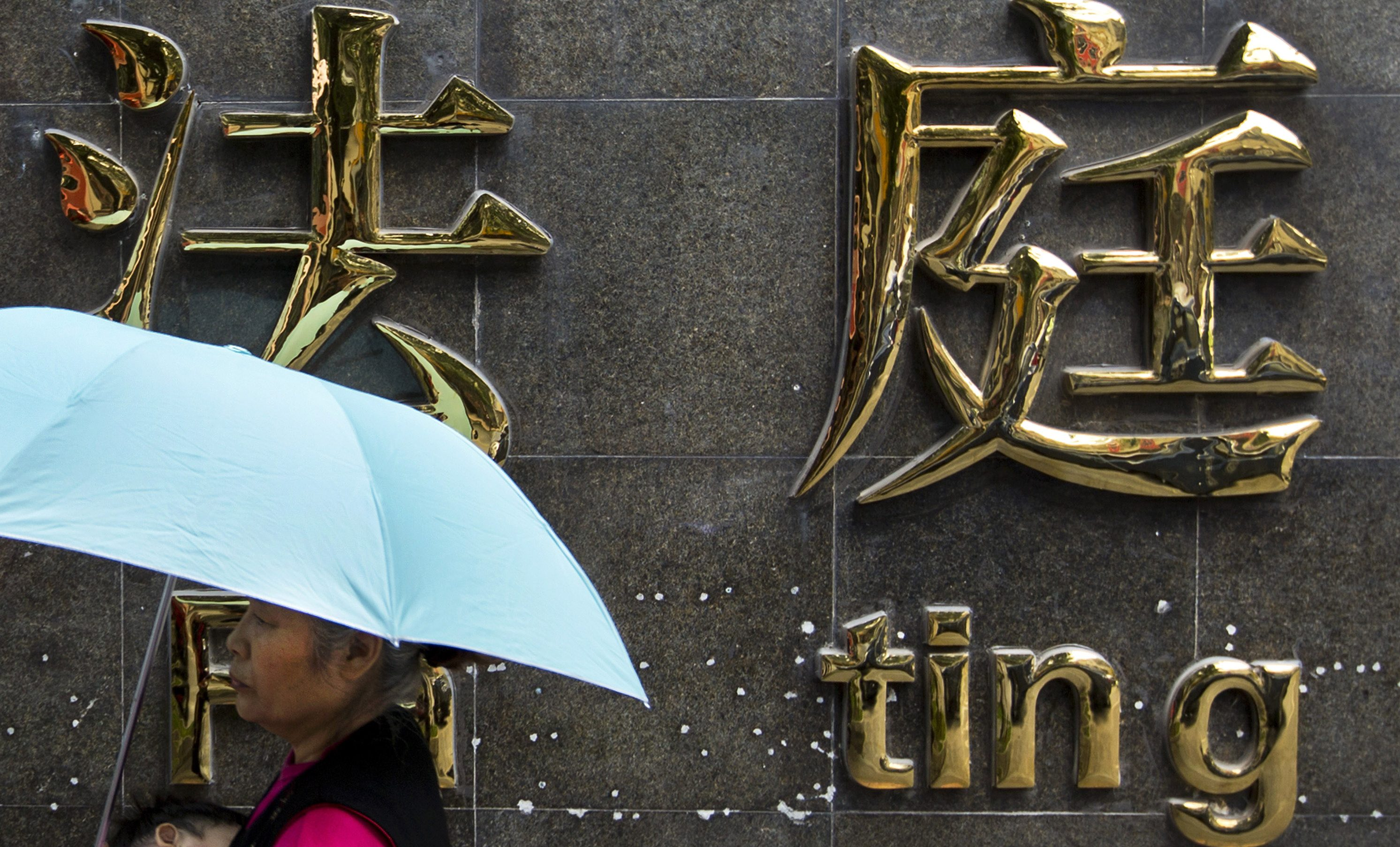 A woman carrying an infant walks past the Chengdu Intermediate Court in Sichuan, Sept. 23, 2012.