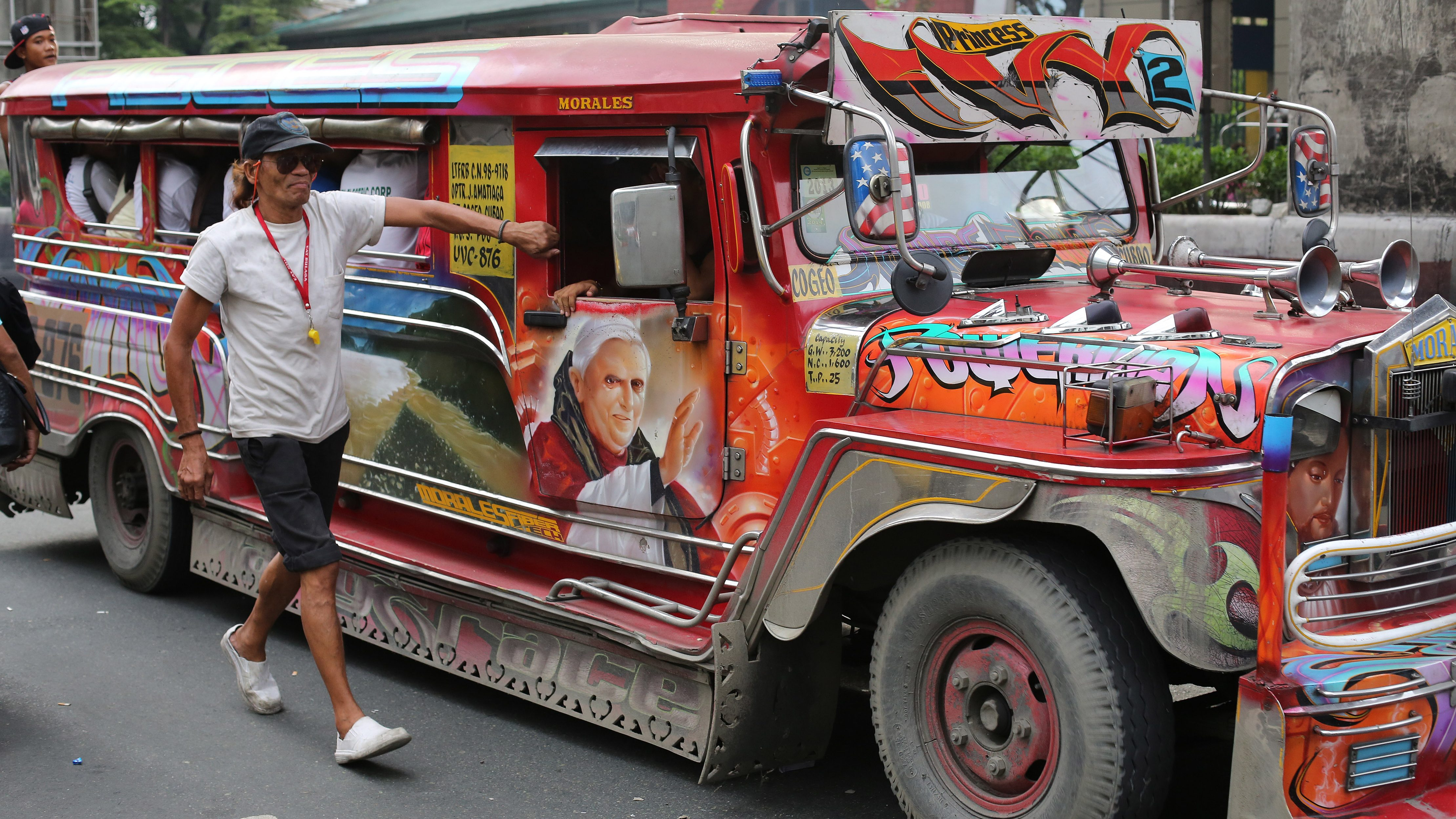 A painting of Pope Emeritus Benedict XVI from Germany decorates a jeepney as a man walks beside it to call for passengers in suburban Quezon City, north of Manila, Philippines on Tuesday, July 8, 2014. Passenger jeepneys are popular means of public transportation in the country. They come in various colors and are sometimes decorated with paintings of religious images and icons in Asia's most prominent Roman Catholic nation.