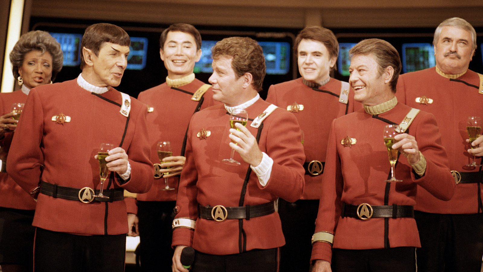 """Members of the """"Star Trek"""" crew, from right in front: DeForest Kelley, William Shanter and Leonard Nimoy, and back row from right: James Doohan, Walter Koenig, George Takei and Nichelle Nichols, toast the newest """"Trek"""" film--in which Shanter makes his directorial debut--""""Star Trek V: The Final Frontier,"""" during a news conference Dec. 28, 1988 at Paramount Studios to announce the latest voyage. (AP Photo/Bob Galbraith)"""