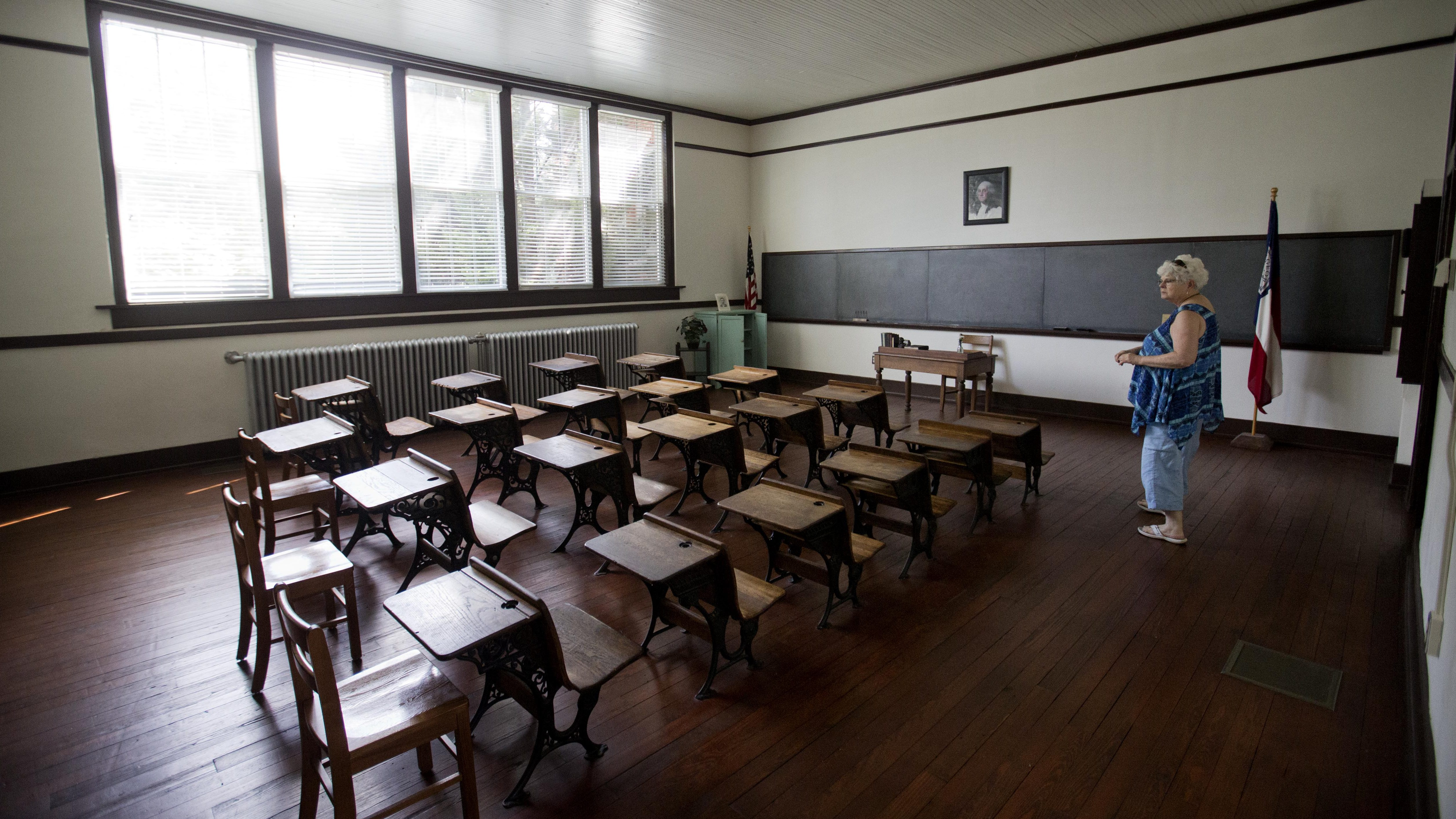 Jane Gurley, of Hendersonville, N.C., walks through a classroom of former President Jimmy Carter from when he attended Plains High School circa 1937, exhibited in what is now the Jimmy Carter National Historic Site in his hometown, Saturday, Aug. 22, 2015, in Plains, Ga. Carter and his hometown have always been intertwined, from the day he announced he would run for president and an old train depot downtown became a local campaign office. He and his wife, Rosalynn, have always kept a home there, but the 90-year-old Carter intends to spend a lot more time in the tiny town as he's treated for cancer that has spread to his brain. (AP Photo/David Goldman)