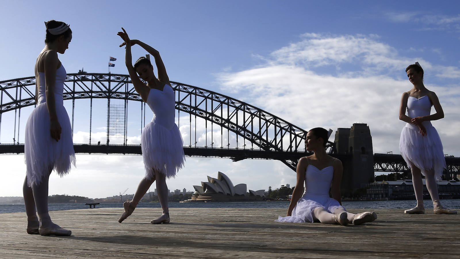 Ballerinas from The Australian Ballet perform on a floating platform, during a promotional event in front of the Sydney Opera House and Harbour Bridge, February 18, 2015. The event was to promote the Australian Ballet's upcoming performance of Swan Lake opening on February 20.   REUTERS/David Gray     (AUSTRALIA - Tags: ENTERTAINMENT SOCIETY TPX IMAGES OF THE DAY) - RTR4Q09B