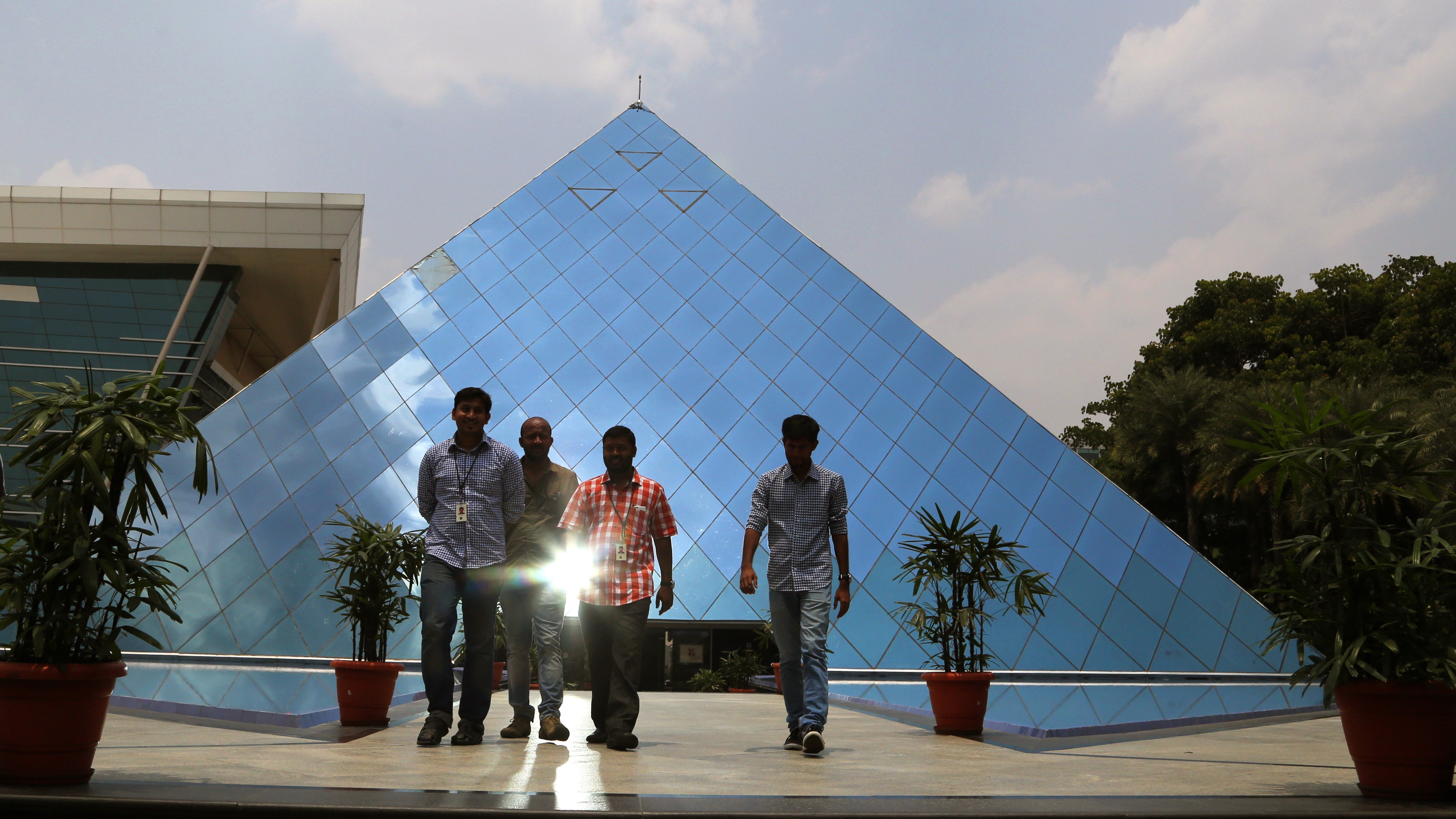 Infosys employees leave a pyramid shaped building at their company's headquarters in Bangalore, India, Friday, April 15, 2016. (AP Photo/Aijaz Rahi)