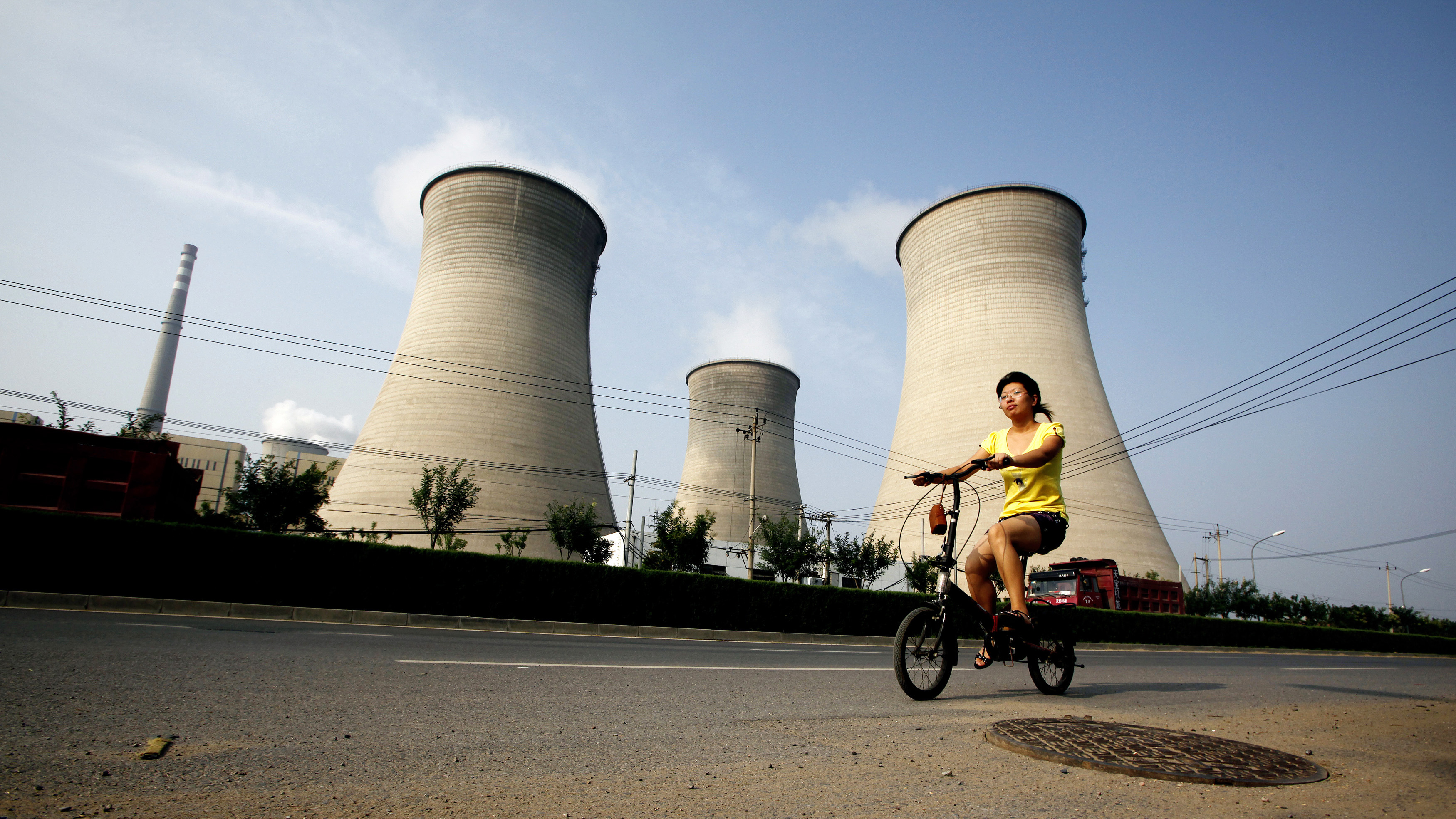 A woman rides her bicycle along a road past a coal-burning power station in Beijing August 12, 2010. China's plans to launch a series of pilot carbon trading projects starting next year underscores its need to curb its soaring greenhouse gas emissions -- now believed to be the world's largest. To match Analysis CHINA-CARBON/ REUTERS/David Gray  (CHINA - Tags: ENERGY ENVIRONMENT SOCIETY IMAGES OF THE DAY) - RTR2H9TO