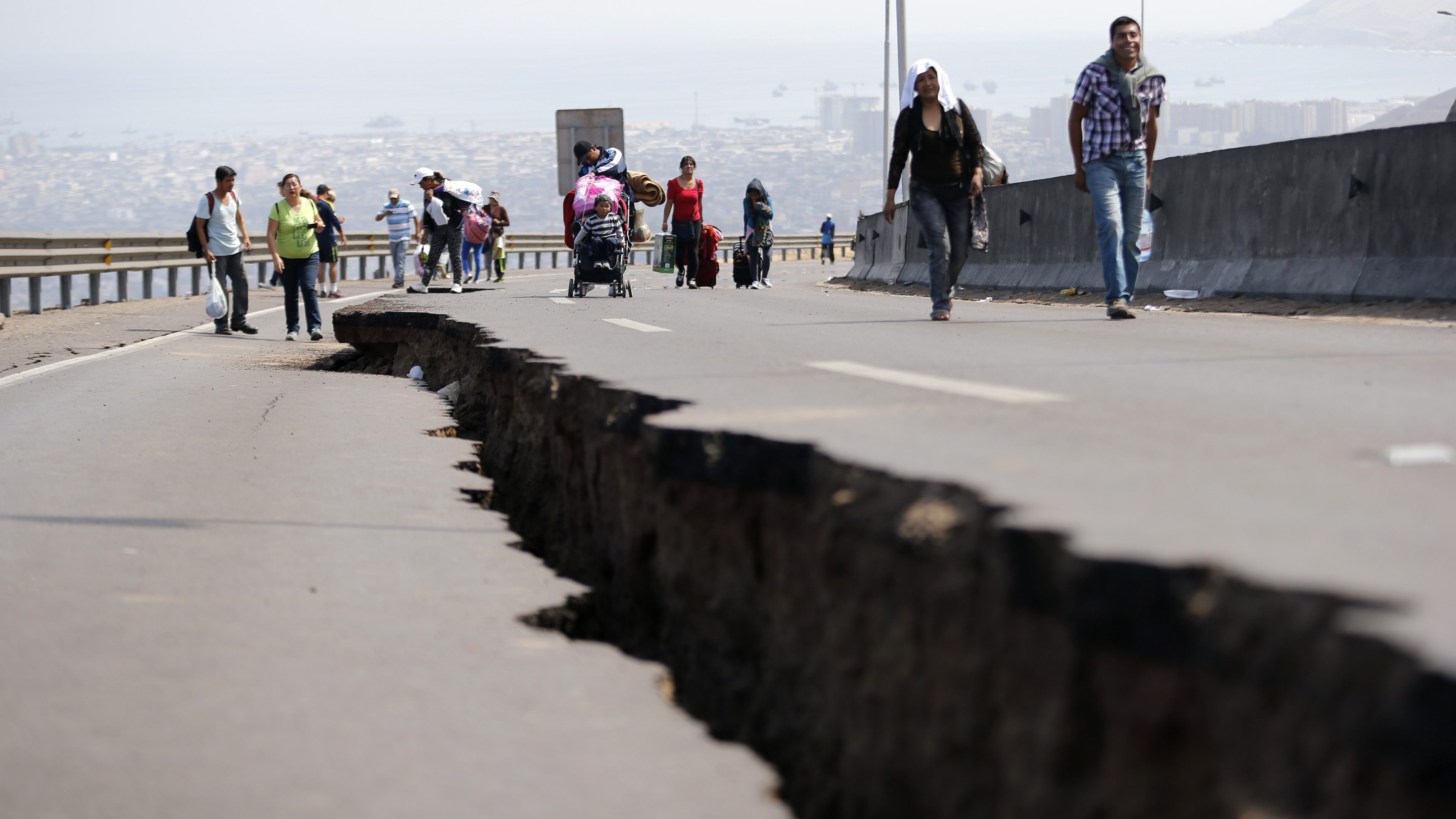 People walk next to a crack along a damaged road leading to Alto Hospicio commune, after a series of aftershocks, in the northern port of Iquique April 3, 2014. A powerful 7.6-magnitude earthquake struck off northern Chile late on Wednesday but there were no reports of damage and a precautionary tsunami alert along the coast and in neighboring Peru was called off.