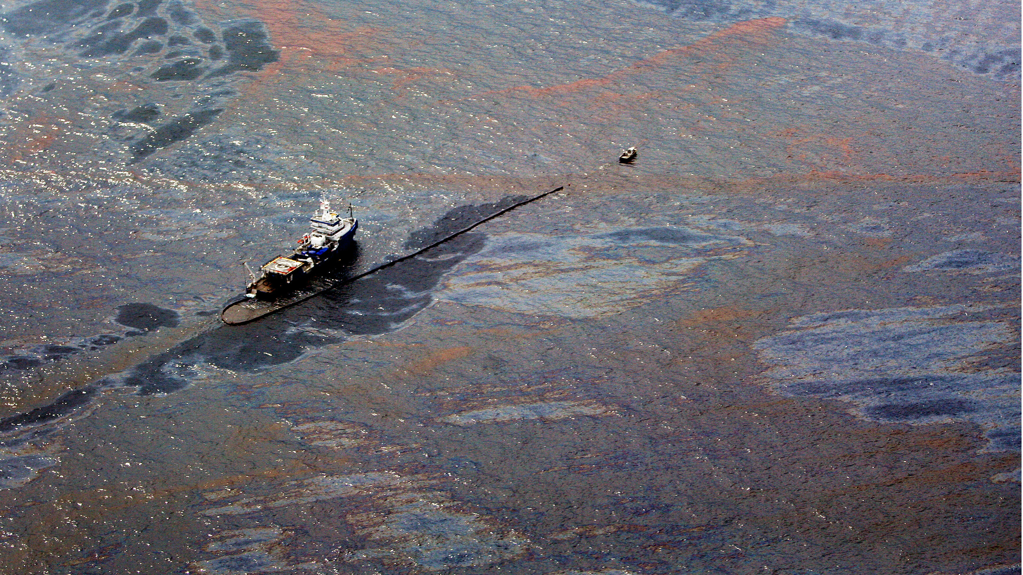 Oil floats on the surface of the Gulf of Mexico around a work boat at the site of the Deepwater Horizon oil spill in the Gulf of Mexico June 2, 2010. As the desperate effort to contain the gusher proceeded, the slick stretched farther. Tar balls and other oil debris from the giant, fragmented slick reached Alabama's Dauphin Island, parts of Mississippi and were less than 16 km (10 miles) from Florida's northwest Panhandle coast.