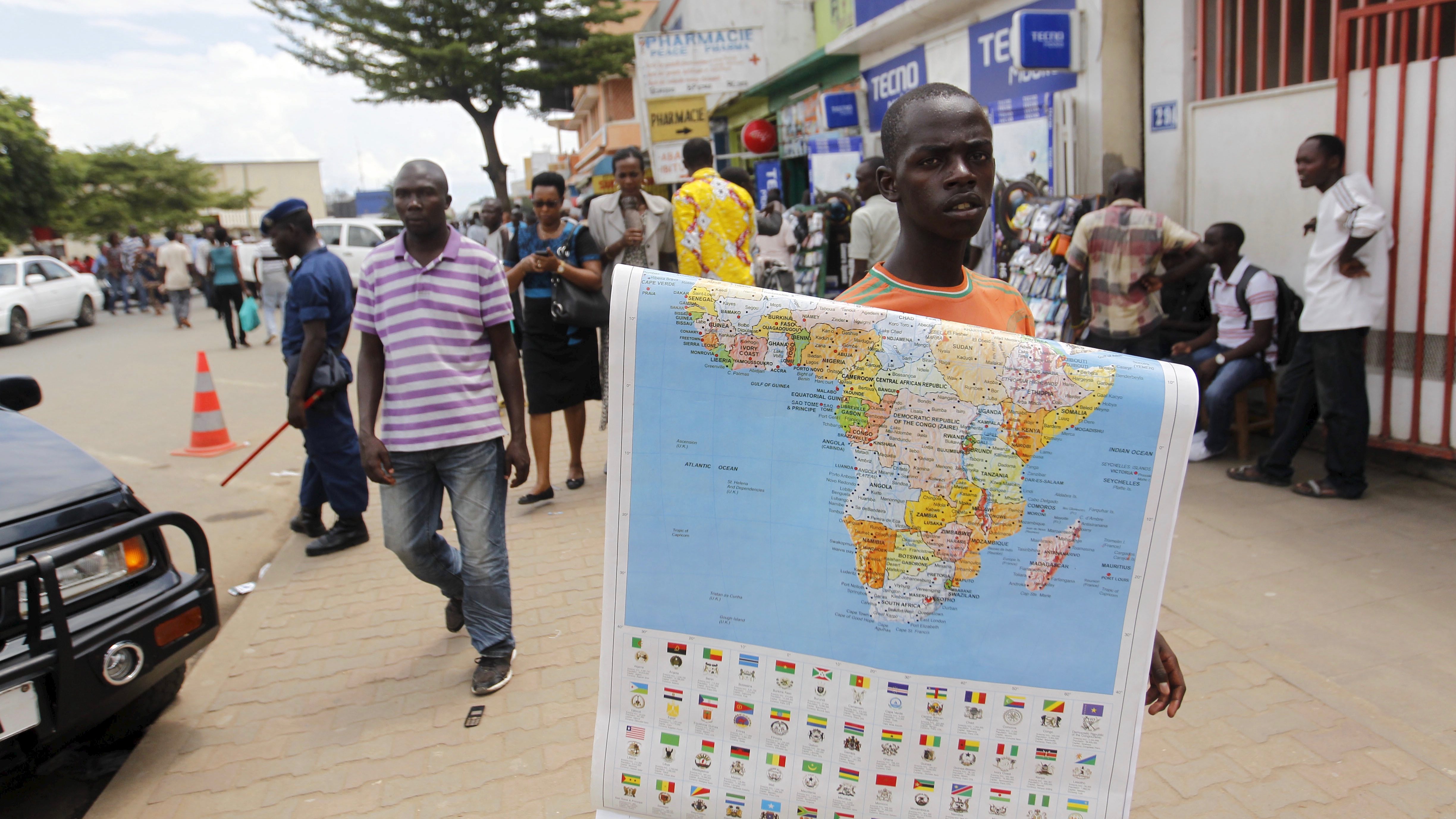 """A vendor sells a map of Africa along the streets of Bujumbura, Burundi April 24, 2015. While recent unrest has plunged the small, landlocked nation of Burundi into its worst crisis since the end of a conflict a decade ago, Reuters photographer Thomas Mukoya shows the realities of daily life. Amid rising tensions in a region with a history of ethnic conflict, crowds of cheering, singing people streamed onto the streets of Bujumbura, the capital of Burundi, on a day that may amount to a coup prompted by a bid by President Pierre Nkurunziza to seek a third term in office. REUTERS/Thomas Mukoya    PICTURE 6 OF 31 FOR WIDER IMAGE STORY """"BURUNDI - LIFE BEYOND THE PROTESTS"""" SEARCH """"MUKOYA BUJUMBURA"""" FOR ALL IMAGES - RTX1CSLJ"""