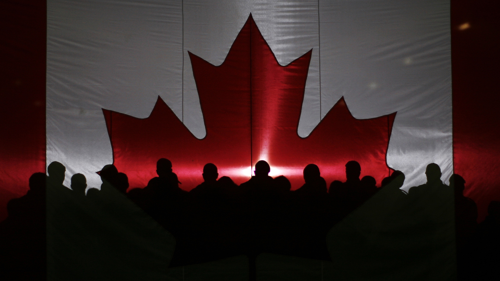 Members of the military and emergency personnel are silhouetted through a Canadian flag while waiting for the start of an event with Canadian Prime Minister Stephen Harper (not pictured) in Resolute Bay, Nunavut August 23, 2011.  REUTERS/Chris Wattie (CANADA - Tags: POLITICS IMAGES OF THE DAY) - RTR2Q8UZ