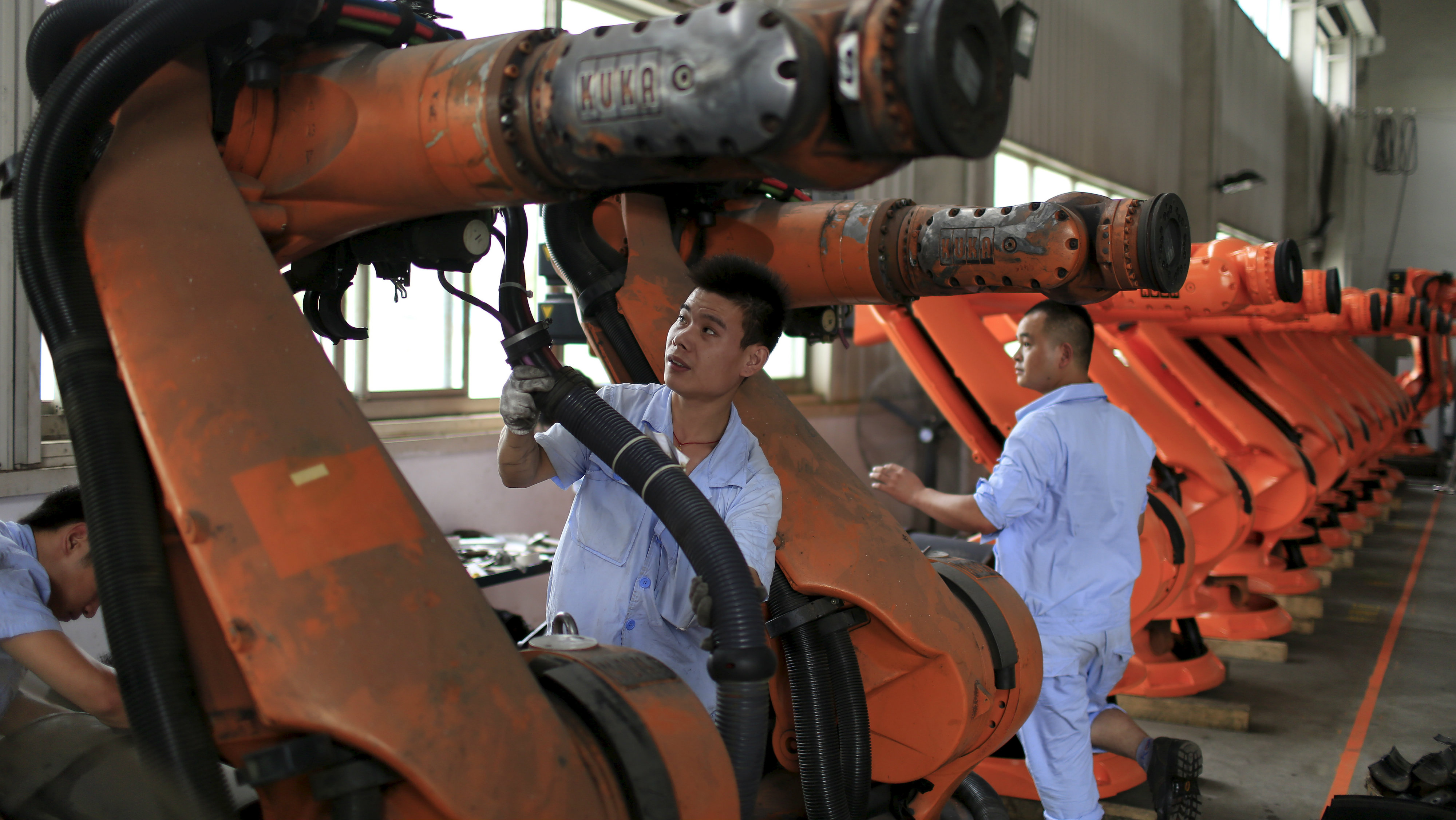 Workers fix second-hand robots in a factory in Shanghai, August 21, 2015. More than a hundred second-hand robots used to make Audi A3s at a German car factory are going through refurbishment at a Wecan Group factory in Shanghai.