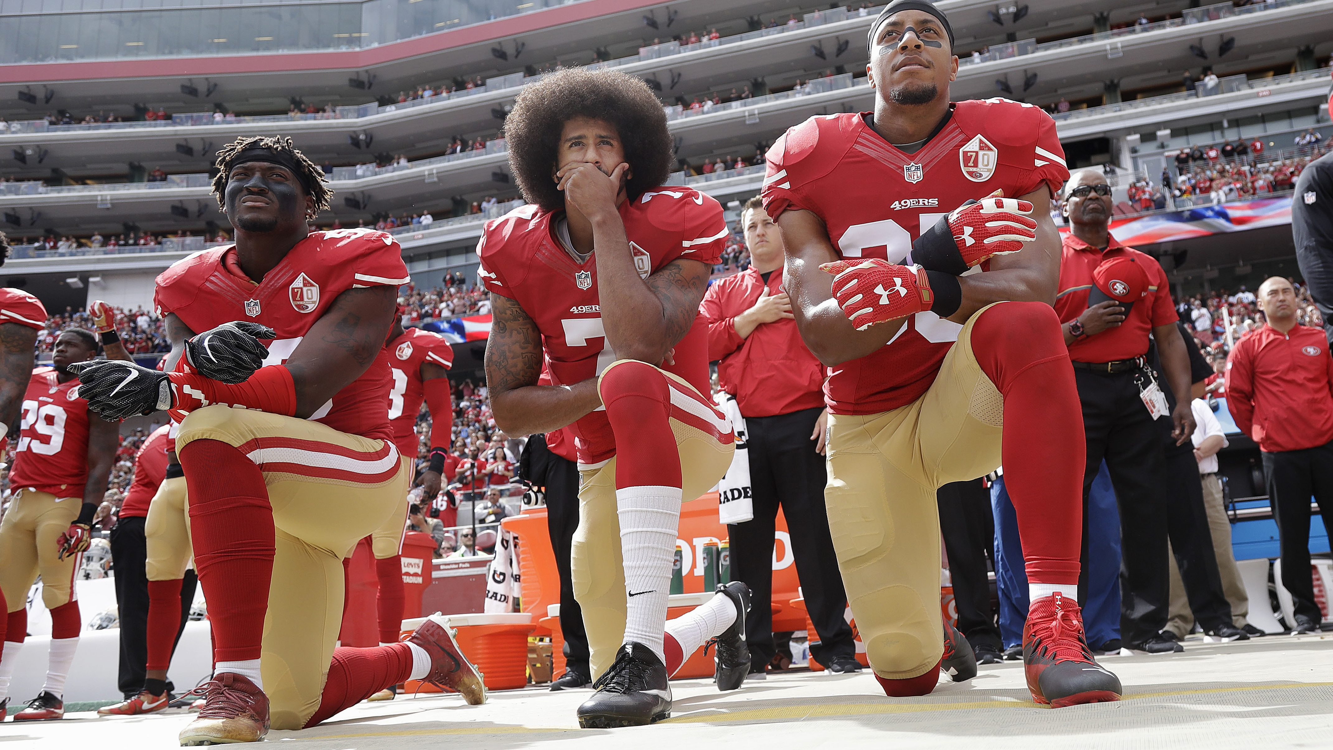 In this Oct. 2, 2016 file photo, from left, San Francisco 49ers outside linebacker Eli Harold, quarterback Colin Kaepernick and safety Eric Reid kneel during the national anthem before an NFL football game against the Dallas Cowboys in Santa Clara, Calif. Since Kaepernick announced he would not stand for the song in protest of racial discrimination against blacks in the United States, many performers are now rethinking offers to sing the national anthem.