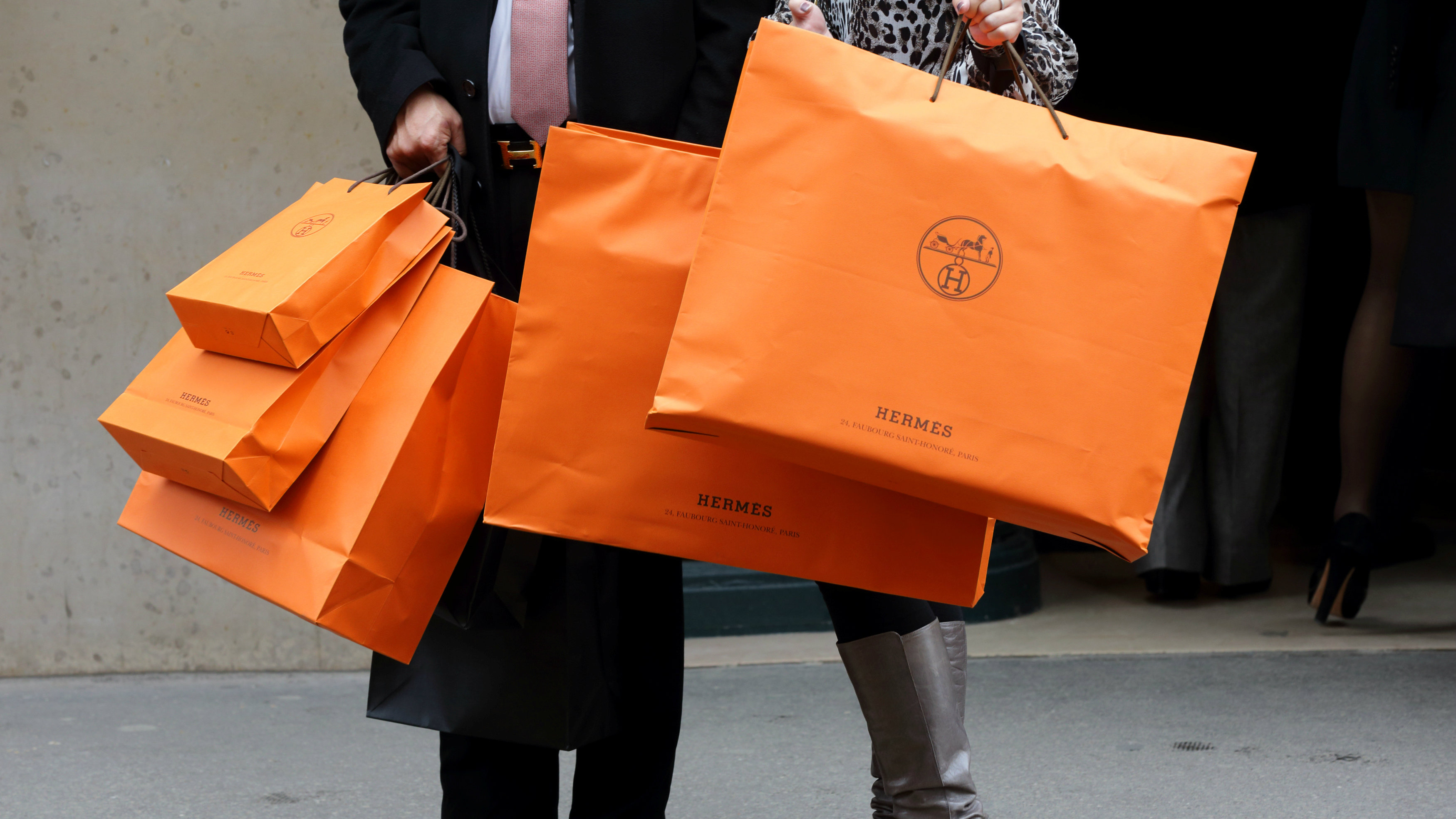 A couple walk with Hermes shopping bags as they leave a Hermes store in Paris, France, March 21, 2013. REUTERS/Philippe Wojazer/File Photo