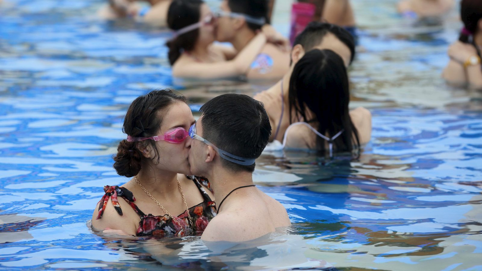Couples kiss at a swimming pool during a kissing contest in Shanghai July 5, 2015. About 20 couples took part in the game and the winning couple who held their kiss for the longest time won a diamond ring, according to local media. Picture taken July 5, 2015.  REUTERS/China Daily CHINA OUT. NO COMMERCIAL OR EDITORIAL SALES IN CHINA - RTX1JBUF