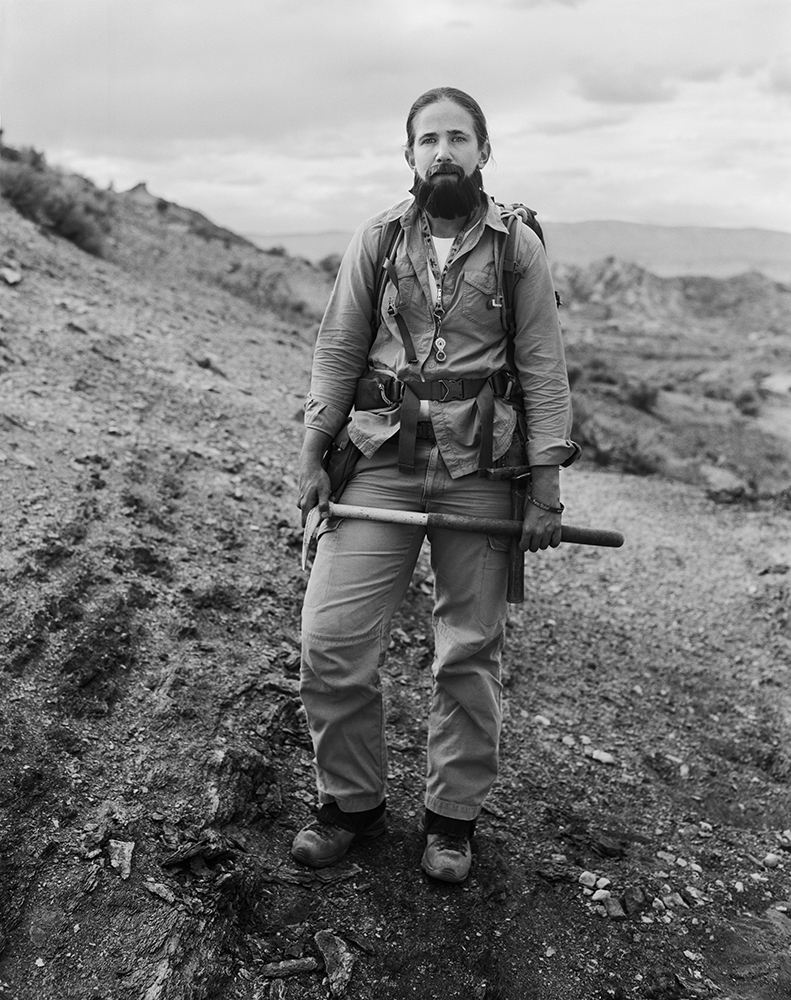 Ellen Currano stands in the field wearing a beard in addition to her usual field work gear.