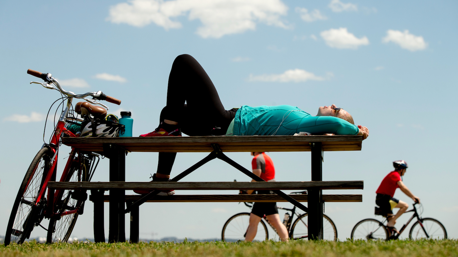 Julia Hurley of Washington relaxes on a picnic table at Gravelly Point Park in Arlington, Va., Wednesday, June 8, 2016, after bicycling to Mt. Vernon and back. (AP Photo/Andrew Harnik)