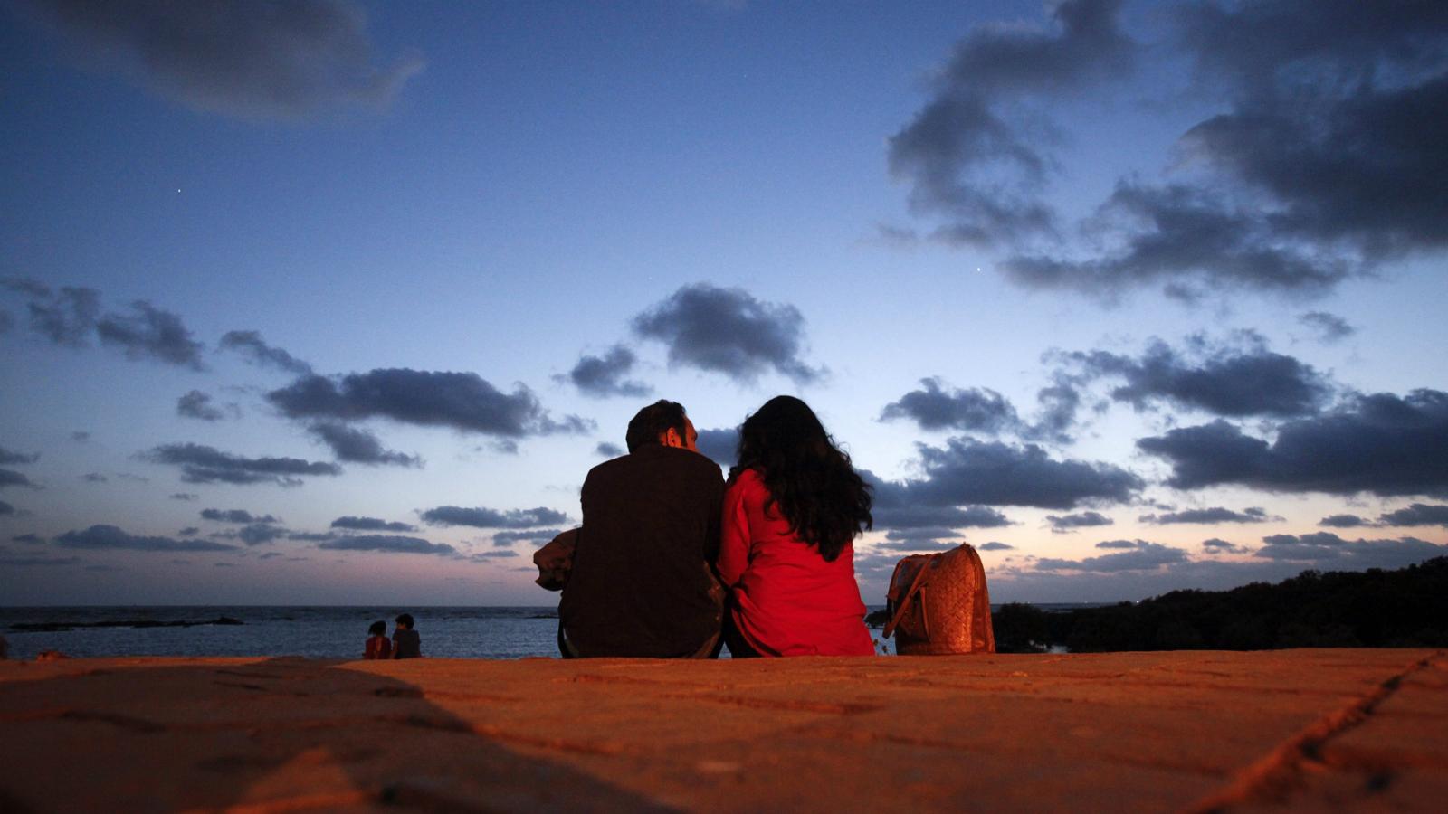 A couple sits along the seafront promenade at dusk in Mumbai's suburbs May 16, 2012.