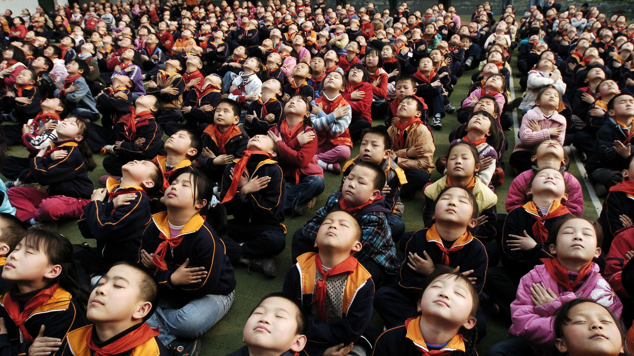 Pupils take a deep breath as they attend a health lecture on how to relax, at a yard of a primary school in Jinan, Shandong province March 31, 2008.