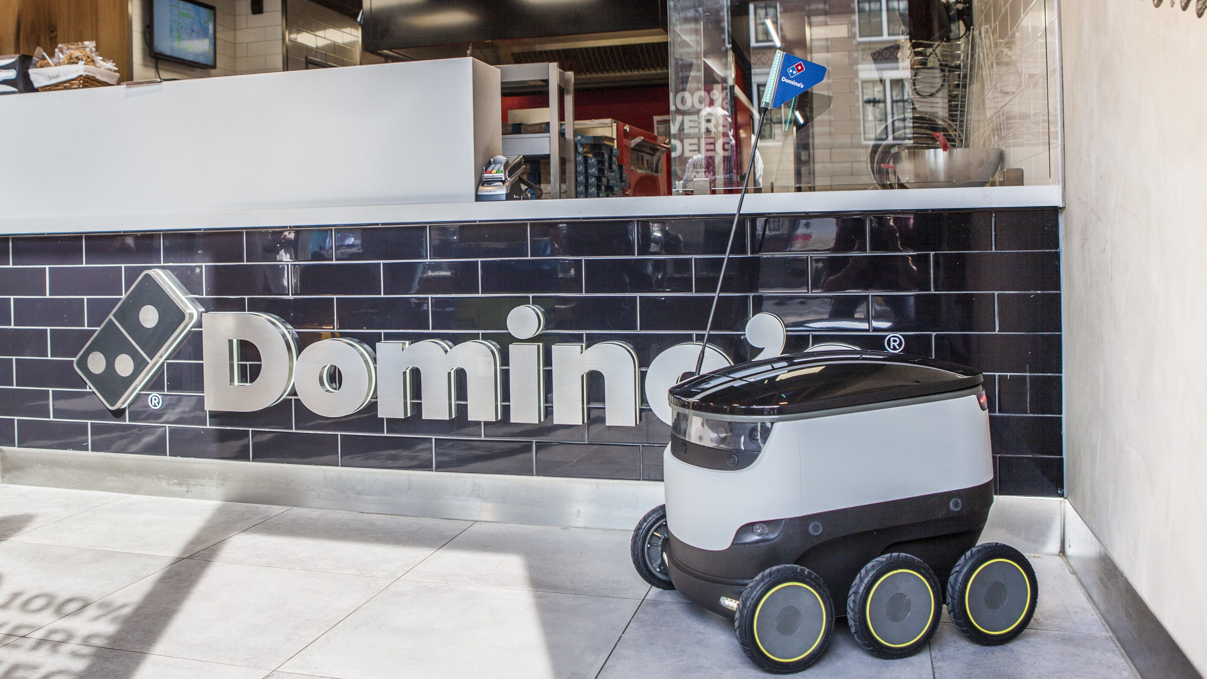 A Starship robot in front of a Domino's counter