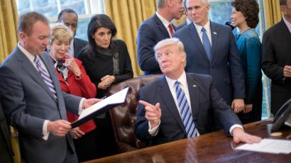 """President Donald Trump looks over towards Budget Director Mick Mulvaney, left, after signing an executive order in the Oval Office of the White House in Washington, Monday, March 13, 2017. Trump signed """"Comprehensive Plan for Reorganizing the Executive Branch"""". From left are, Mulvaney, Small Business Administration Administrator Linda McMahon, Housing and Urban Development Secretary Ben Carson, UN Ambassador Nikki Haley, Interior Secretary Ryan Zinke, Vice President Mike Pence, Transportation Secretary Elaine Chao and Commerce Secretary Wilbur Ross."""