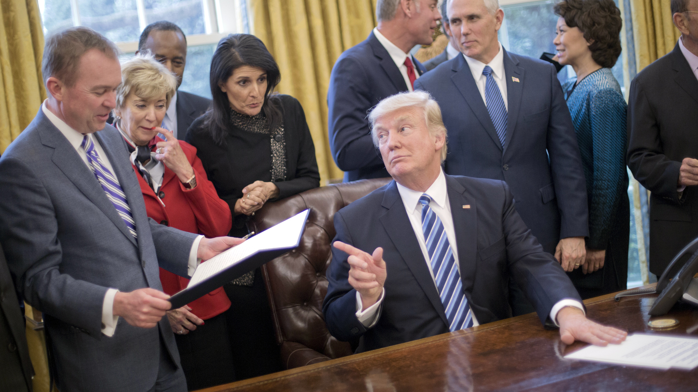 "President Donald Trump looks over towards Budget Director Mick Mulvaney, left, after signing an executive order in the Oval Office of the White House in Washington, Monday, March 13, 2017. Trump signed ""Comprehensive Plan for Reorganizing the Executive Branch"". From left are, Mulvaney, Small Business Administration Administrator Linda McMahon, Housing and Urban Development Secretary Ben Carson, UN Ambassador Nikki Haley, Interior Secretary Ryan Zinke, Vice President Mike Pence, Transportation Secretary Elaine Chao and Commerce Secretary Wilbur Ross."