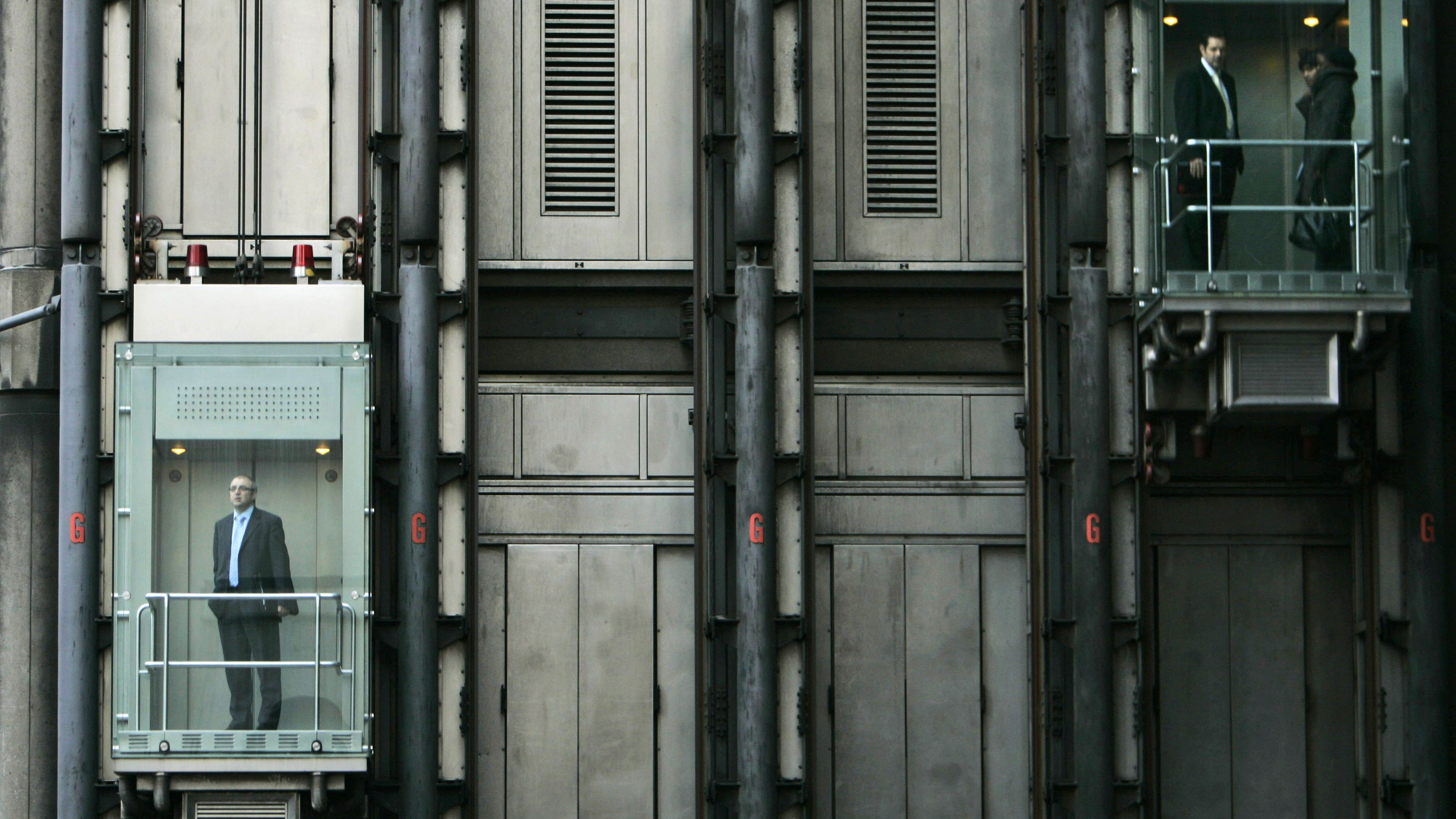 People are seen riding elevators on a building in central London's City financial district.
