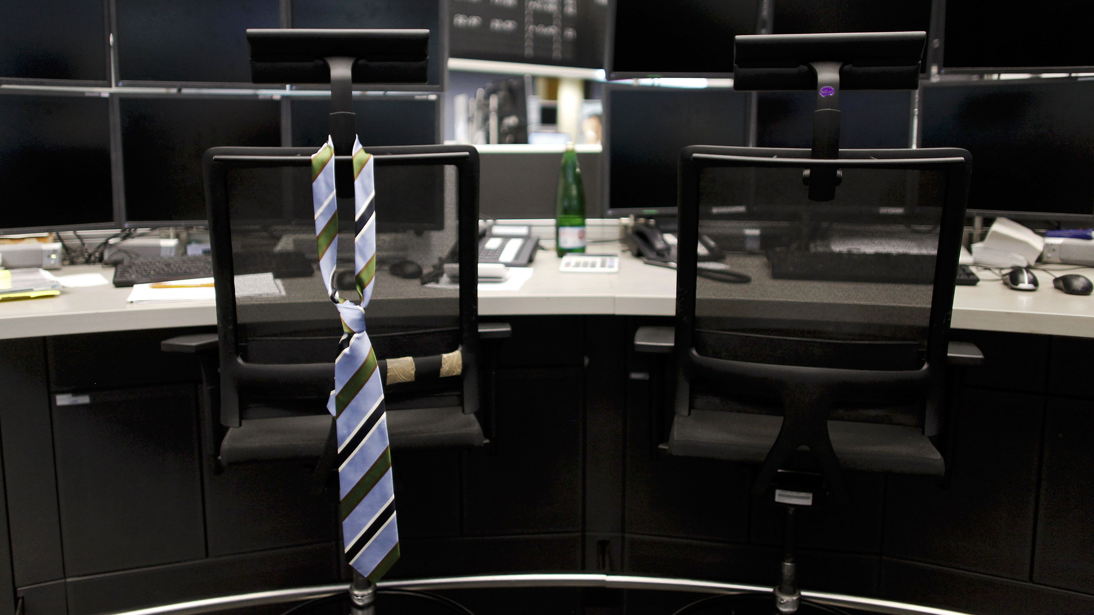 A tie hangs from an empty chair on a trader desk after the end of a trading day at the Frankfurt stock exchange August 12, 2011. REUTERS/Alex Domanski (GERMANY - Tags: BUSINESS IMAGES OF THE DAY)