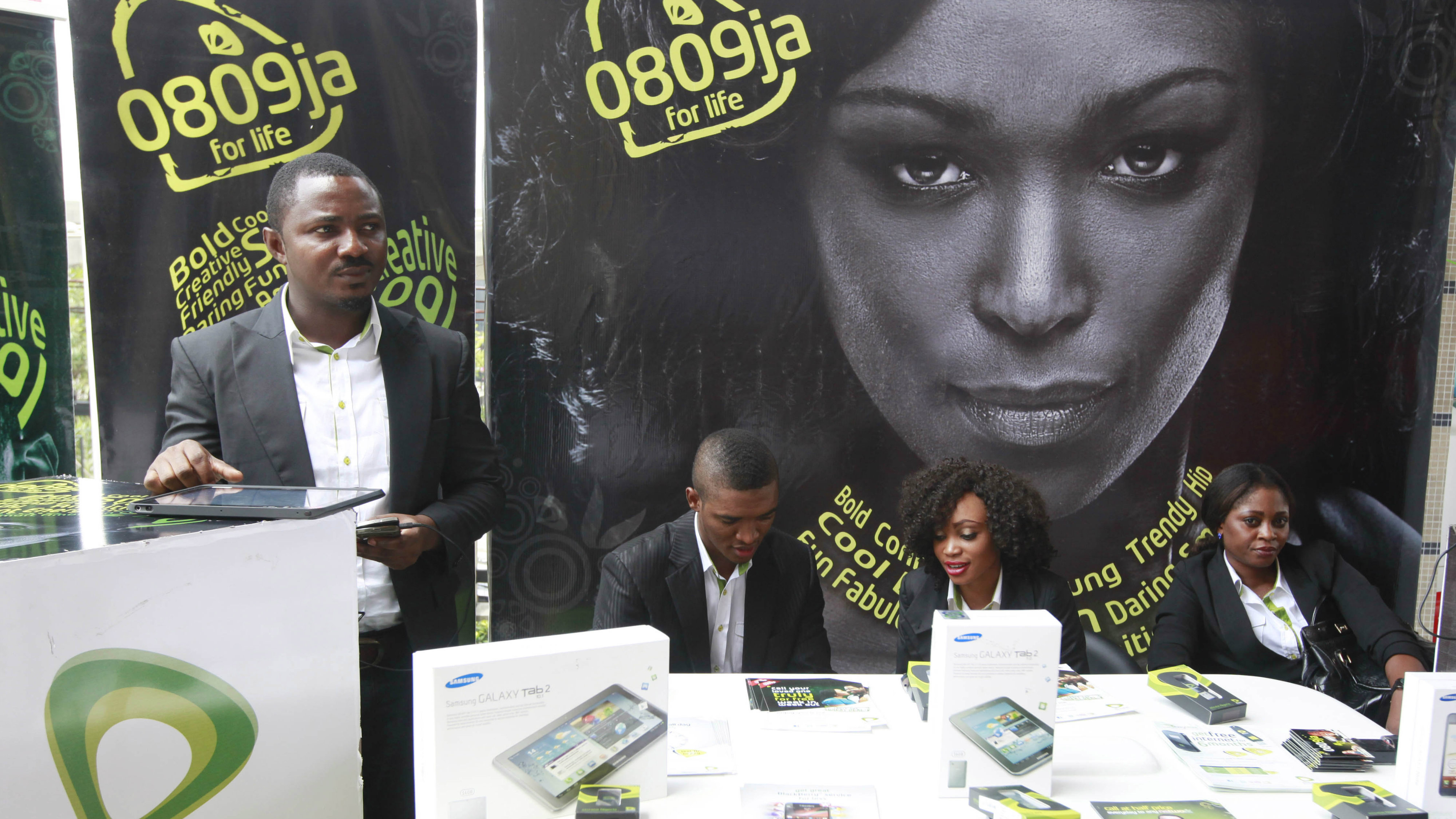 In this Monday, April. 22, 2013 file photo, Staff of Etisalat Nigeria wait for customers during the launch of mobile number portability in Lagos, Nigeria. Nigeria is set to overtake South Africa as the biggest economy in Africa with a long-overdue recount of its GDP that will give it continental bragging rights but do little for its 112 million people scrabbling to survive in desperate poverty. That's cause for reflection in longtime rival South Africa, the only African member of the G20, on the strength of its position as the continent's economic powerhouse. Finance Minister Ngozi Ikonjo-Iweala is to announce new GDP figures on Sunday, April. 6, 2014 to include previously uncounted industries like telecommunications and IT, banking and insurance, music and airlines, and the burgeoning online retail outlets and Nollywood films that didn't exist when the last count was made in 1990. Then, there were 300,000 landlines. Today, Nigeria has 100 million cell phone users.