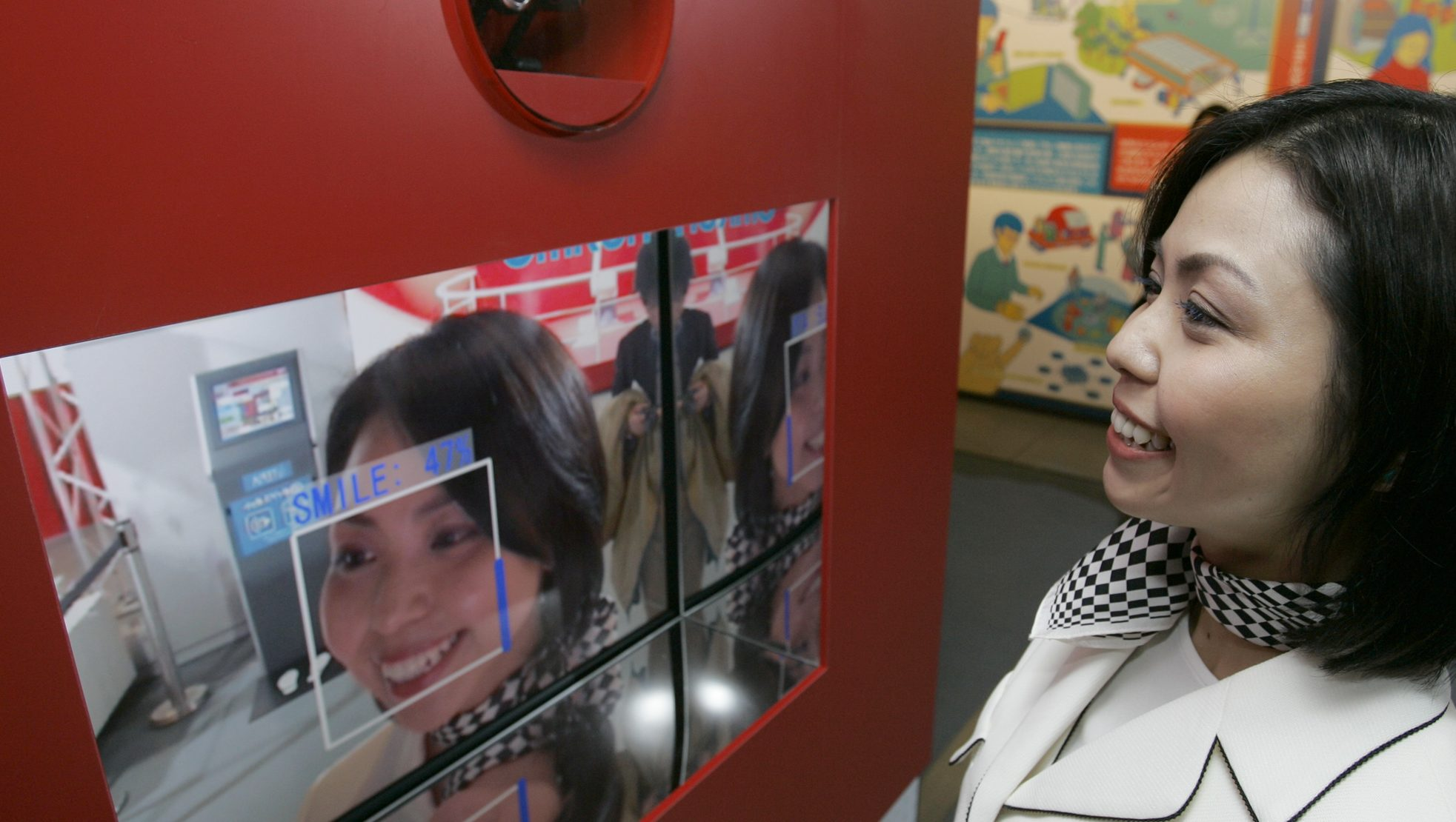 """A woman smiles as she demonstrates Japanese electronics and health-care company Omron Corp.'s Okao Catch, or """"face catch,""""  that can measure how big your smile is during a newly opened  technology exhibition space TEPIA in Tokyo Thursday, April 10, 2008. The software technology scans a video image to detect faces. It can find up to 100 faces in an image, according to Yasushi Kawamoto of Omron. Okao Catch then analyzes curves of the lips, eye movements and other facial expressions to decide how much a person is smiling using data collected from a million people and their smiles, he said."""