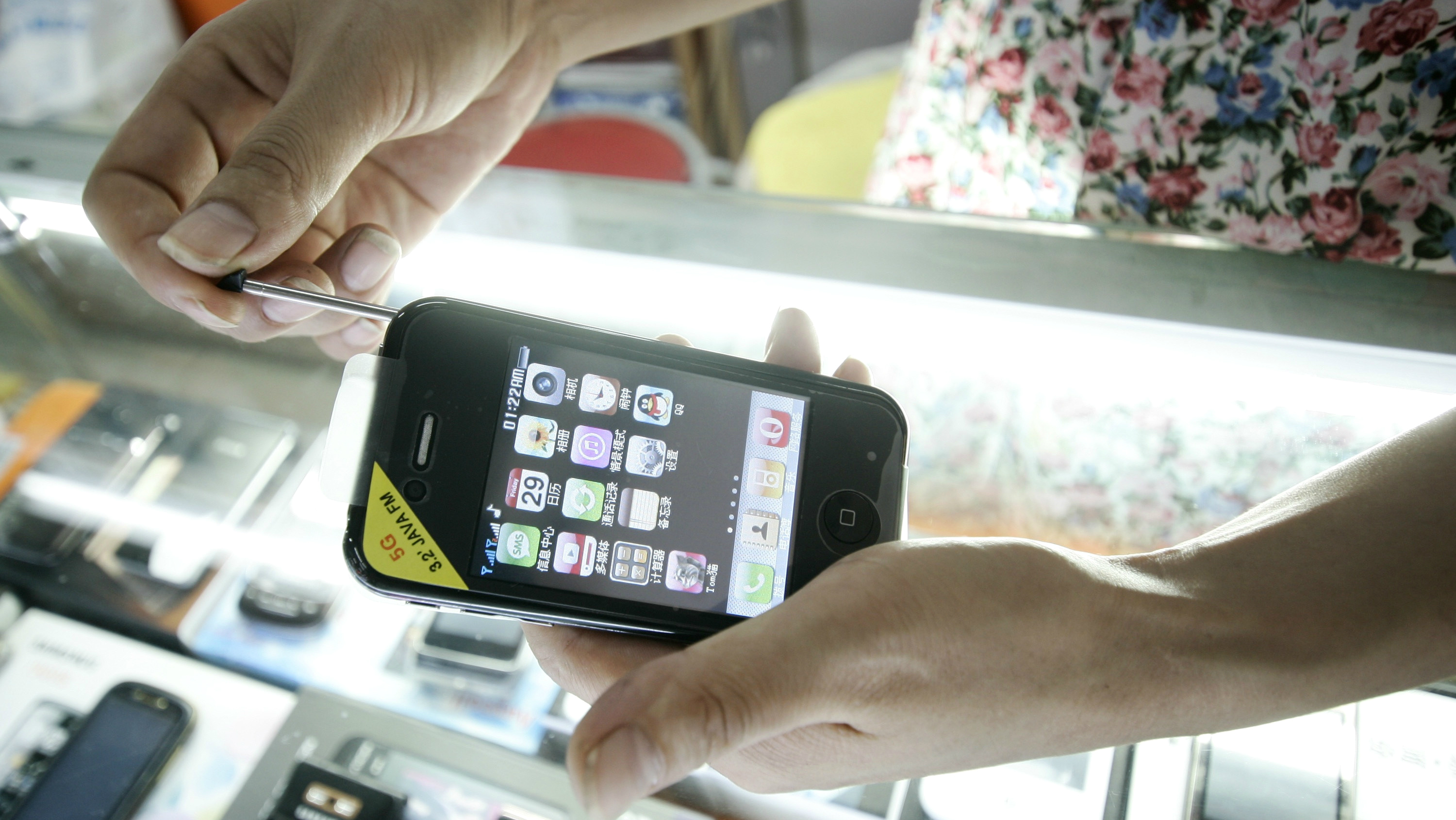 A shop clerk shows a fake iPhone which is sold at a mobile phone market Sunday, Aug. 14 in Shanghai, China.