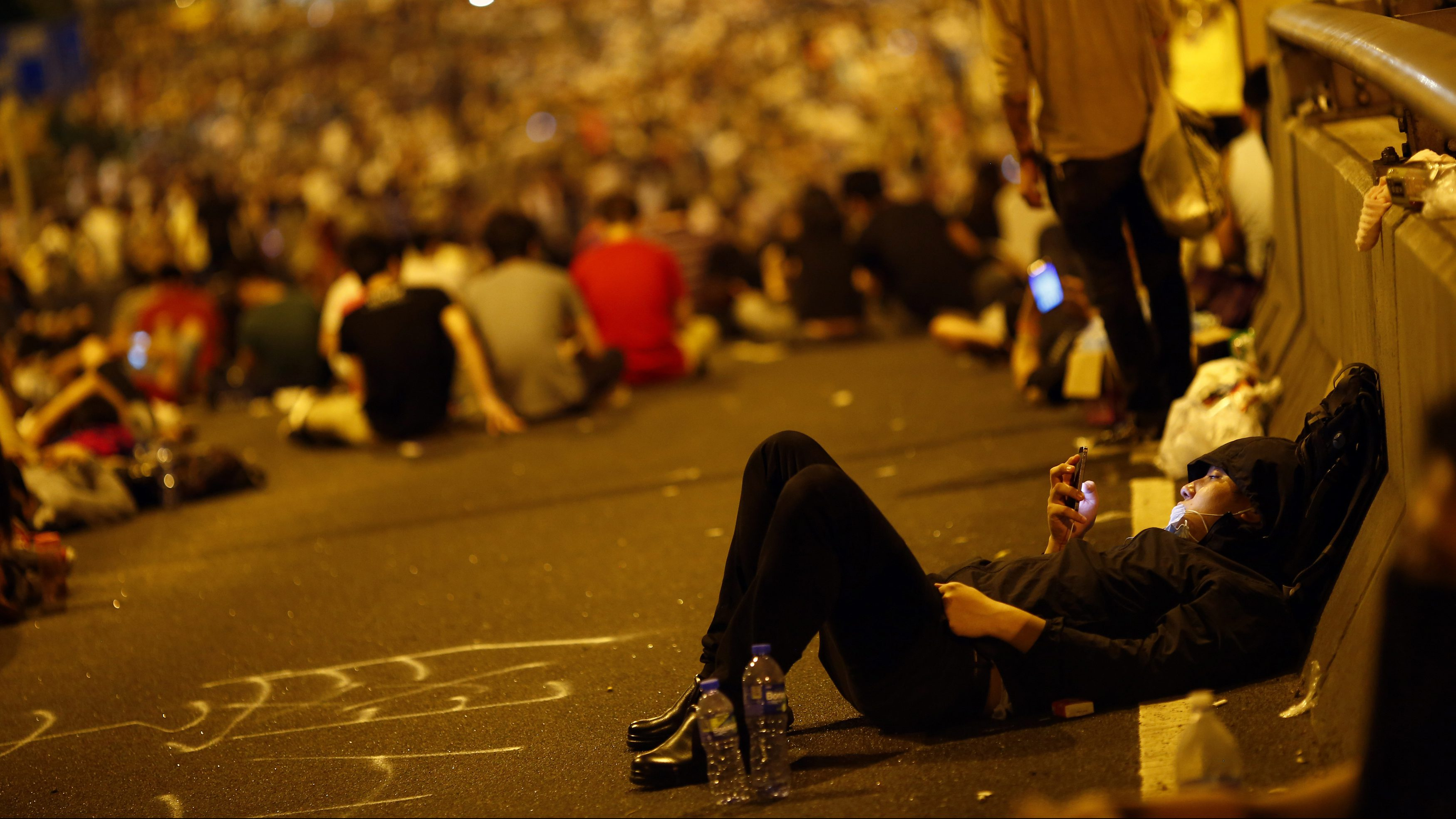 A protester looks at his mobile phone as he and others block the main street to the financial Central district outside the government headquarters in Hong Kong, September 29, 2014. Riot police advanced on Hong Kong democracy protesters in the early hours of Monday, firing volleys of tear gas after launching a baton-charge in the worst unrest there since China took back control of the former British colony two decades ago.