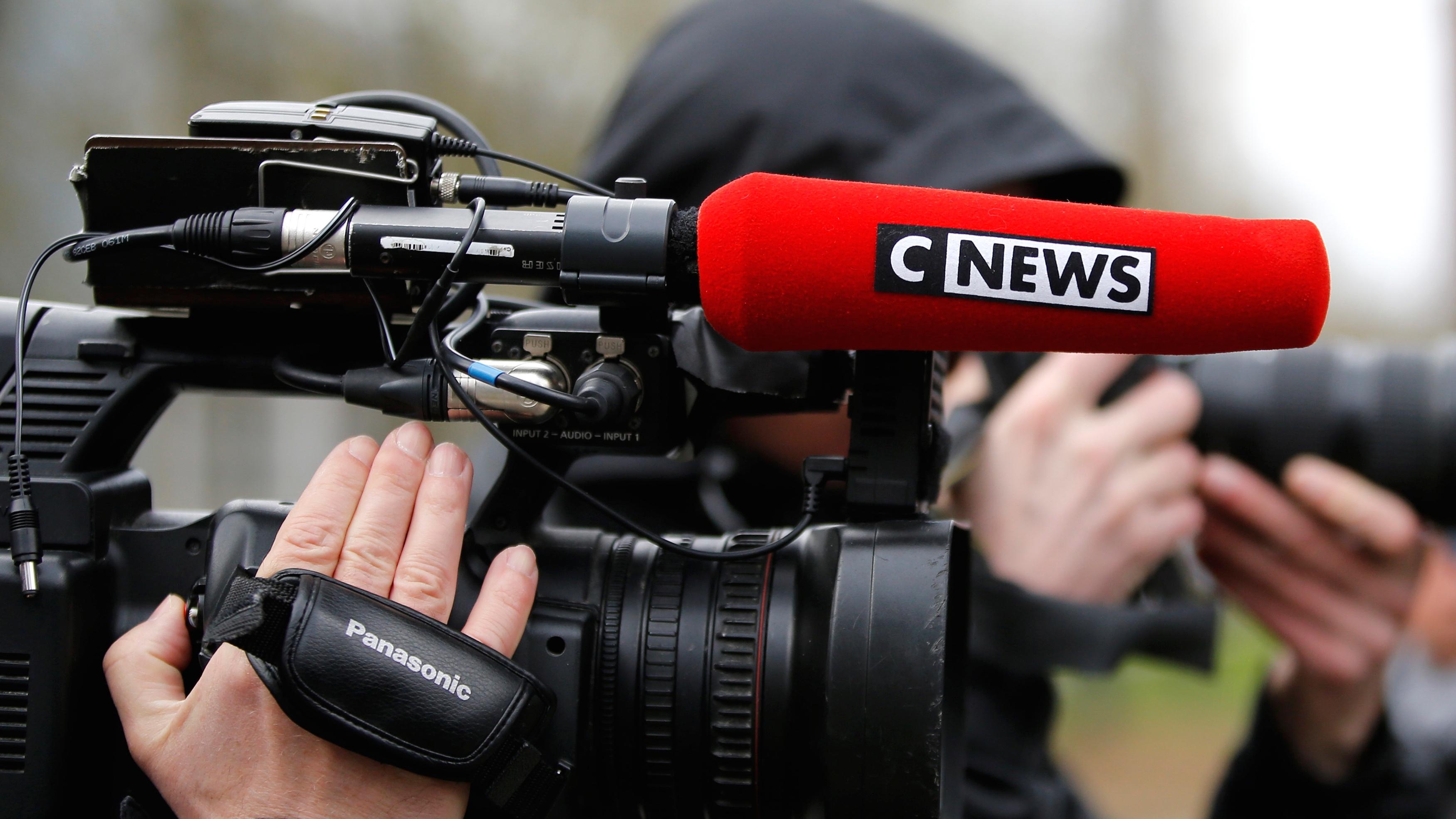 Cameraman holds camera.