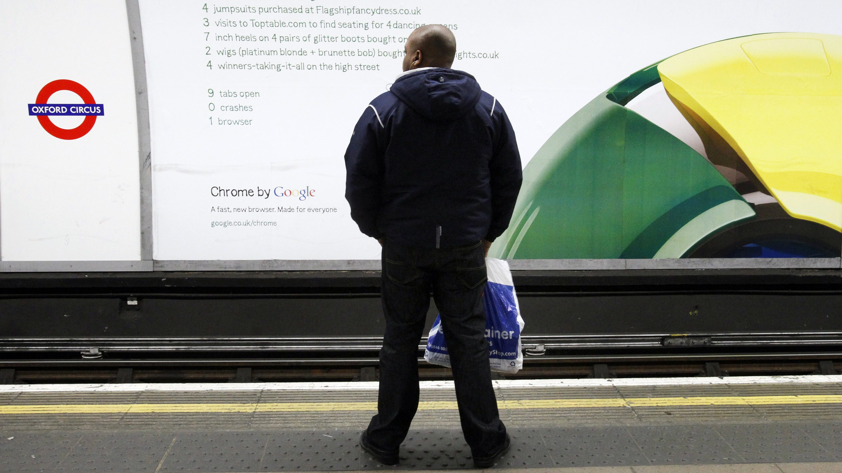 A man waits for a train in front of a poster for Google's Chrome browser in an underground station in London