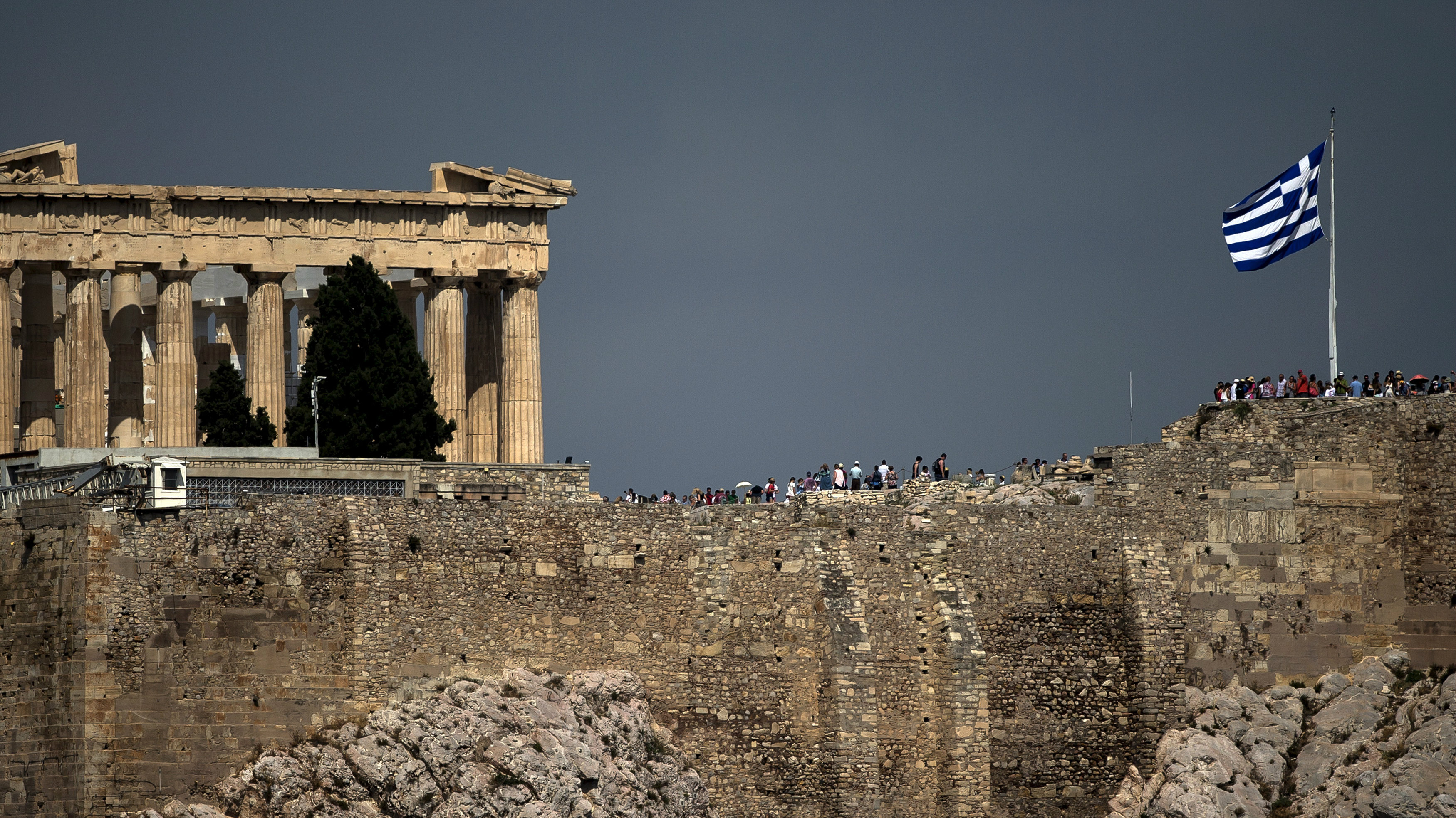 Greek Parthenon with flag in the distance