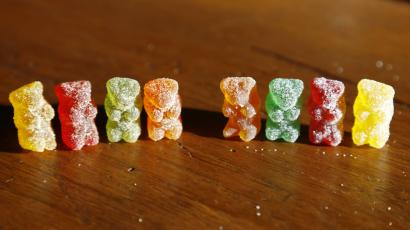 a row of eight gummy bears with sugar coatings. gummies are red, green, orange, and yellow on a wooden table.