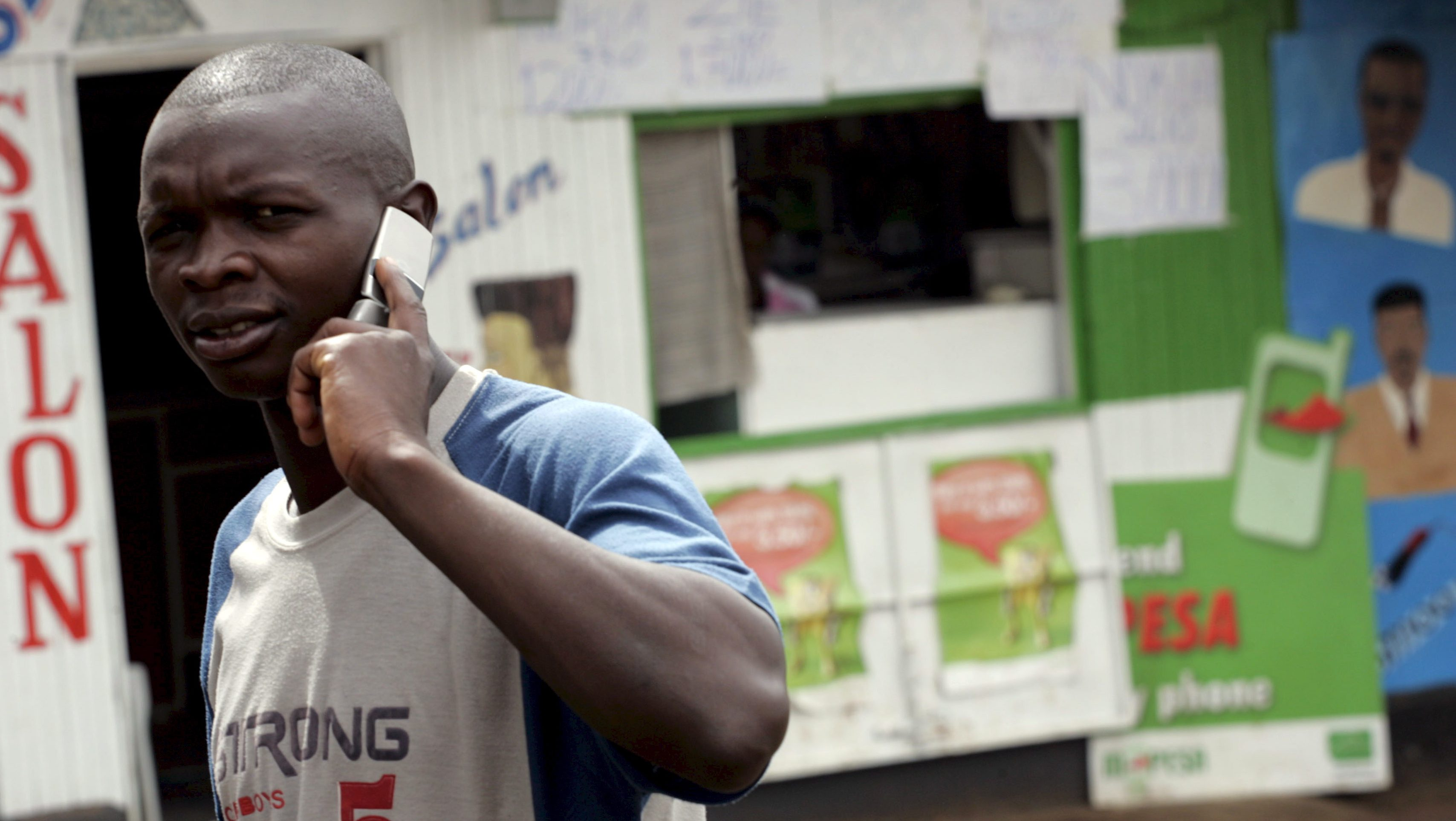 A Kenyan man talks on his mobile while walking through the high density suburb of Kangami in Nairobi, Kenya on 26 March 2008. The Kenyan government plans to sell 25 per cent of its stake in the highly profitable mobile operator Safaricom by holding east Africa's largest ever IPO which is scheduled to begin selling shares on 28 December 2008.