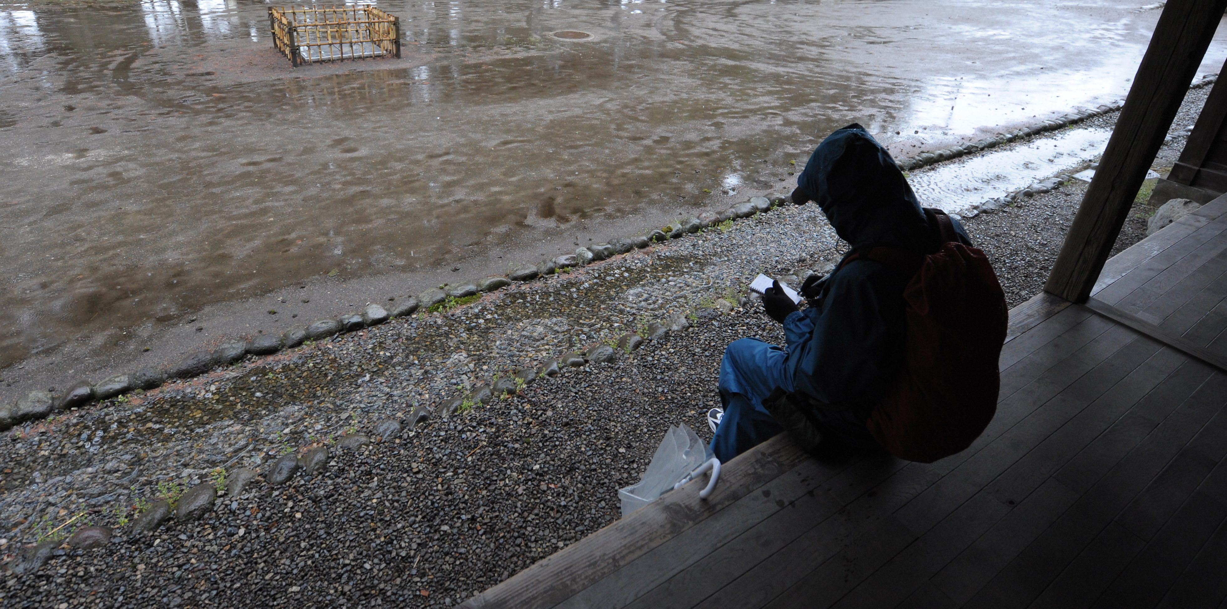 A hikikomori writes a haiku while seeking shelter from heavy rains at a traditional farm house in Nikko, Japan, 28 April 2010.