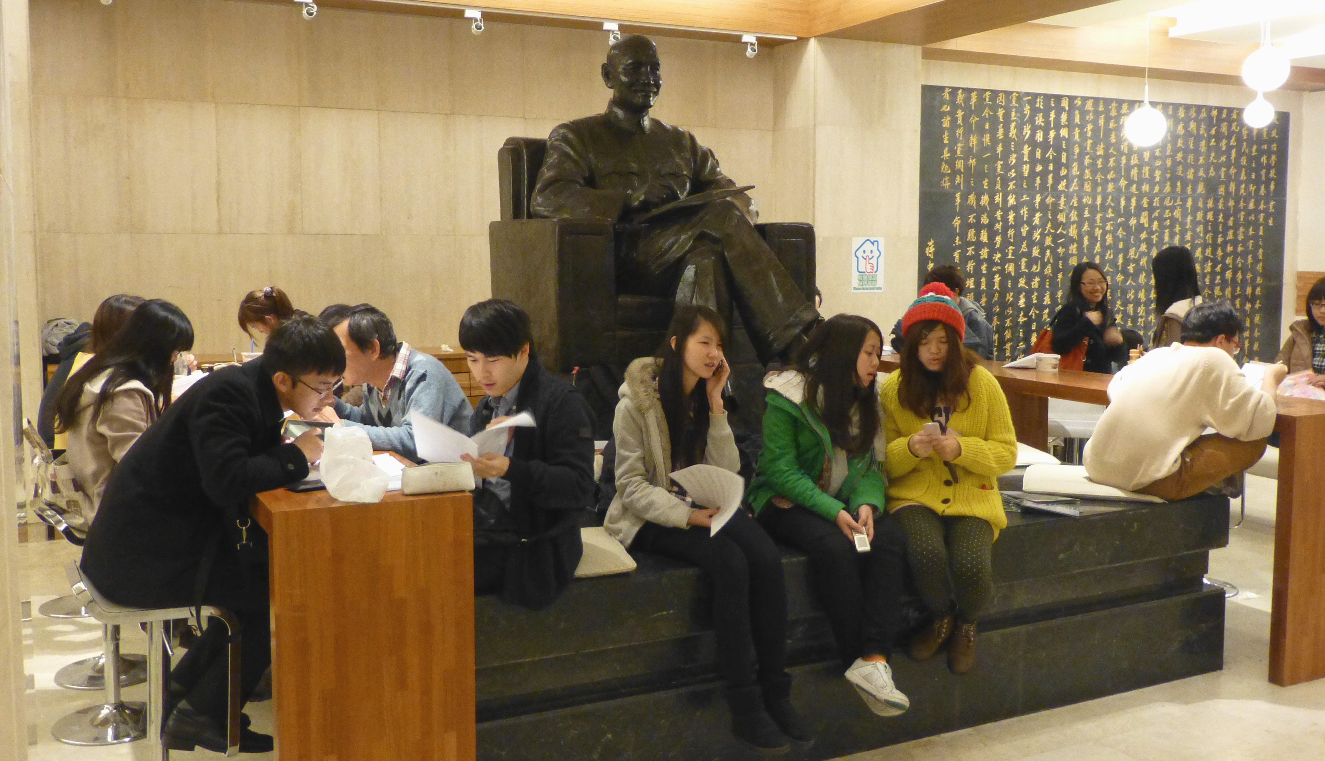 Students read books and prepare lessons beside a statue of late president Chiang Kai-shek in the National Chengchi University library in Taipei, Taiwan, 15 January 2013.