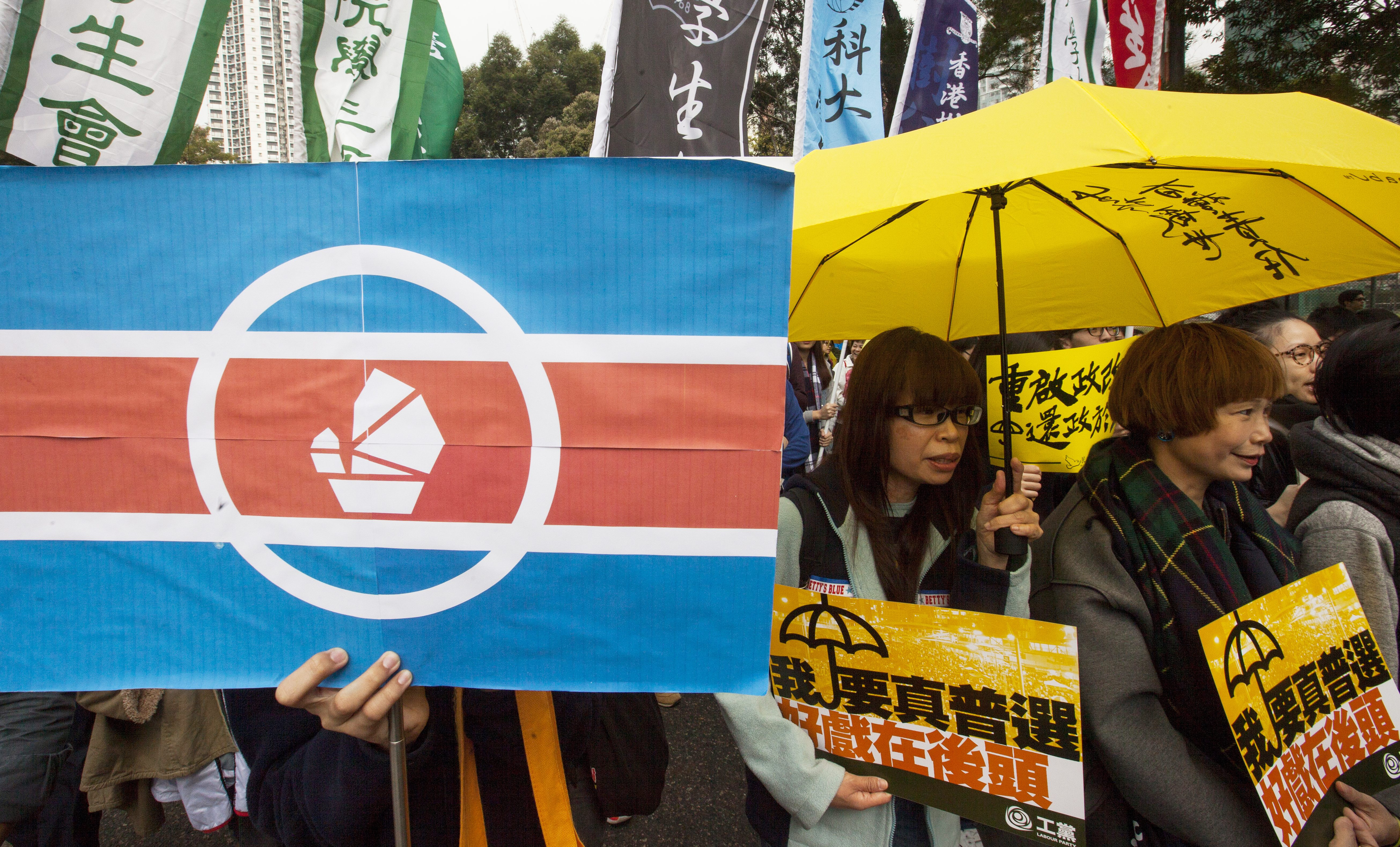 A protestor shows a mock North Korean flag with a Hong Kong junk boat placed in the middle to symbolize what they believe is Hong Kong's repressive political regime, as they march through the streets calling for genuine universal suffrage, Hong Kong, 1 February, 2015.