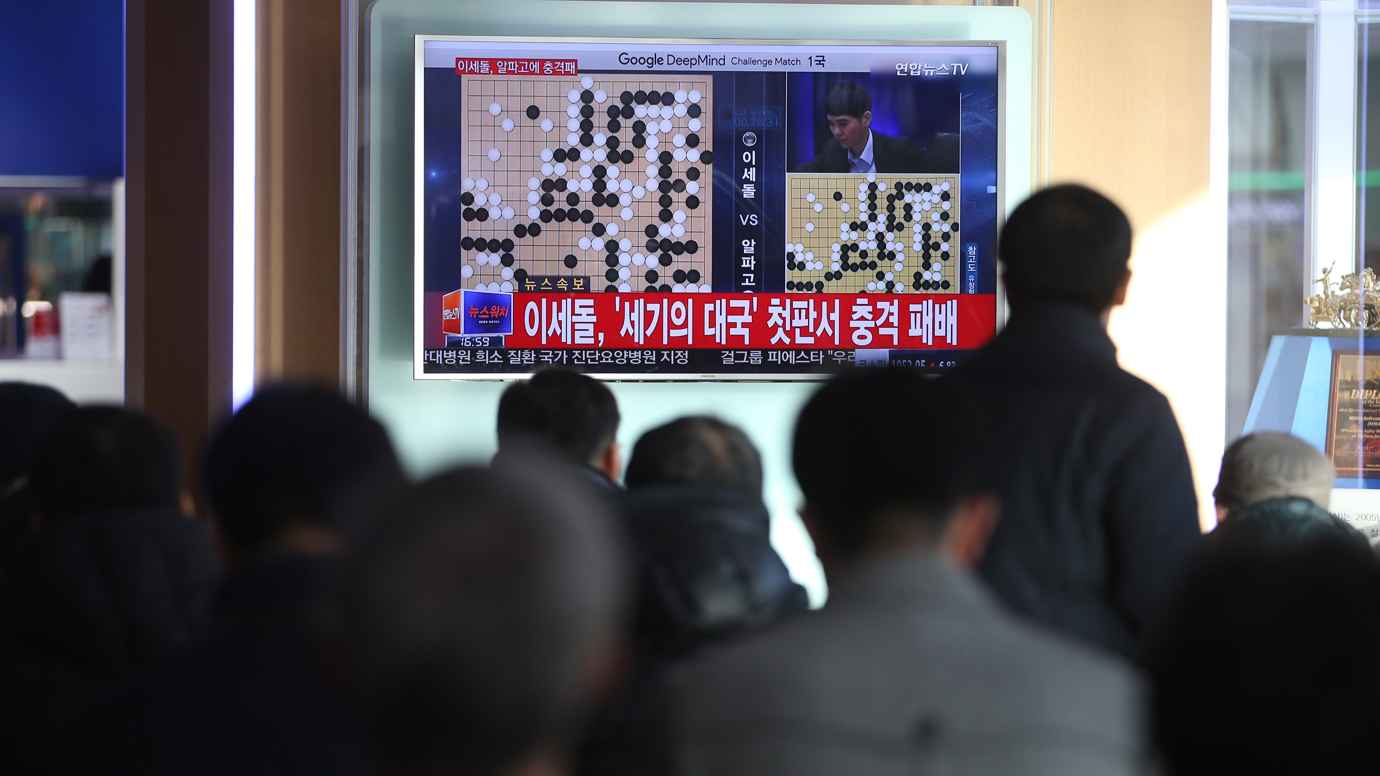 epa05202304 People watch coverage of Go grandmaster Lee Se-dol's loss to the Google-developed artificial intelligence AlphaGo in the first match of the best-of-five series in Seoul, South Korea, 09 March 2016. One of Google's top computer programmes squared off against a human opponent for a five-round match of the boardgame Go on 09 March, in the latest development to pit artificial intelligence against human ingenuity.