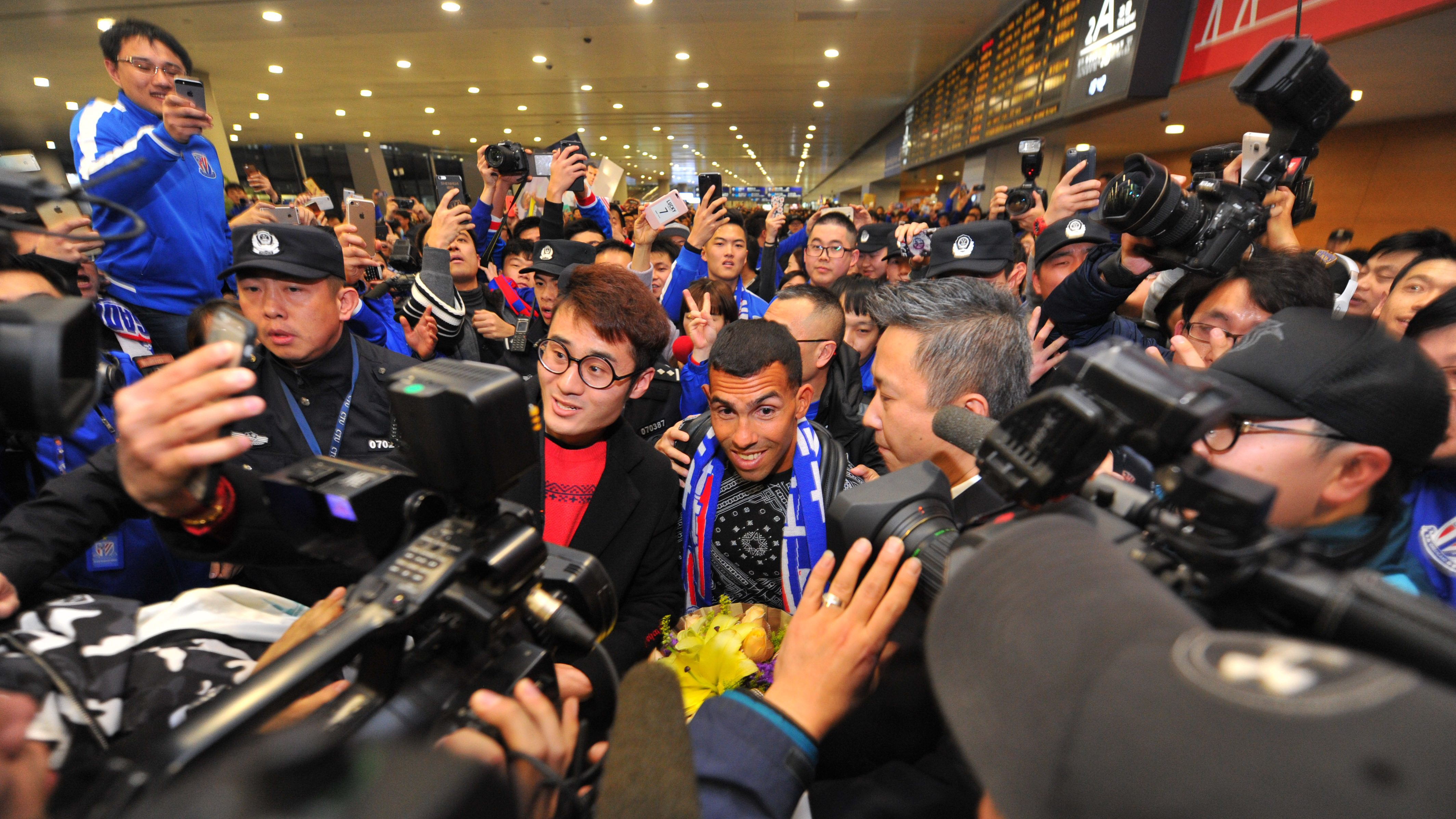 Argentine striker Carlos Tevez (C) makes his way through the crowd of fans upon arrival at Shanghai Pudong International Airport in Shanghai, China, 19 January 2017. The Argentine striker is reportedly to be world's top earning soccer player under his two-year contract with Shanghai Shenhua.