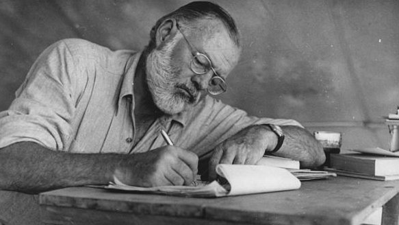 Ernest Hemingway writing at a desk