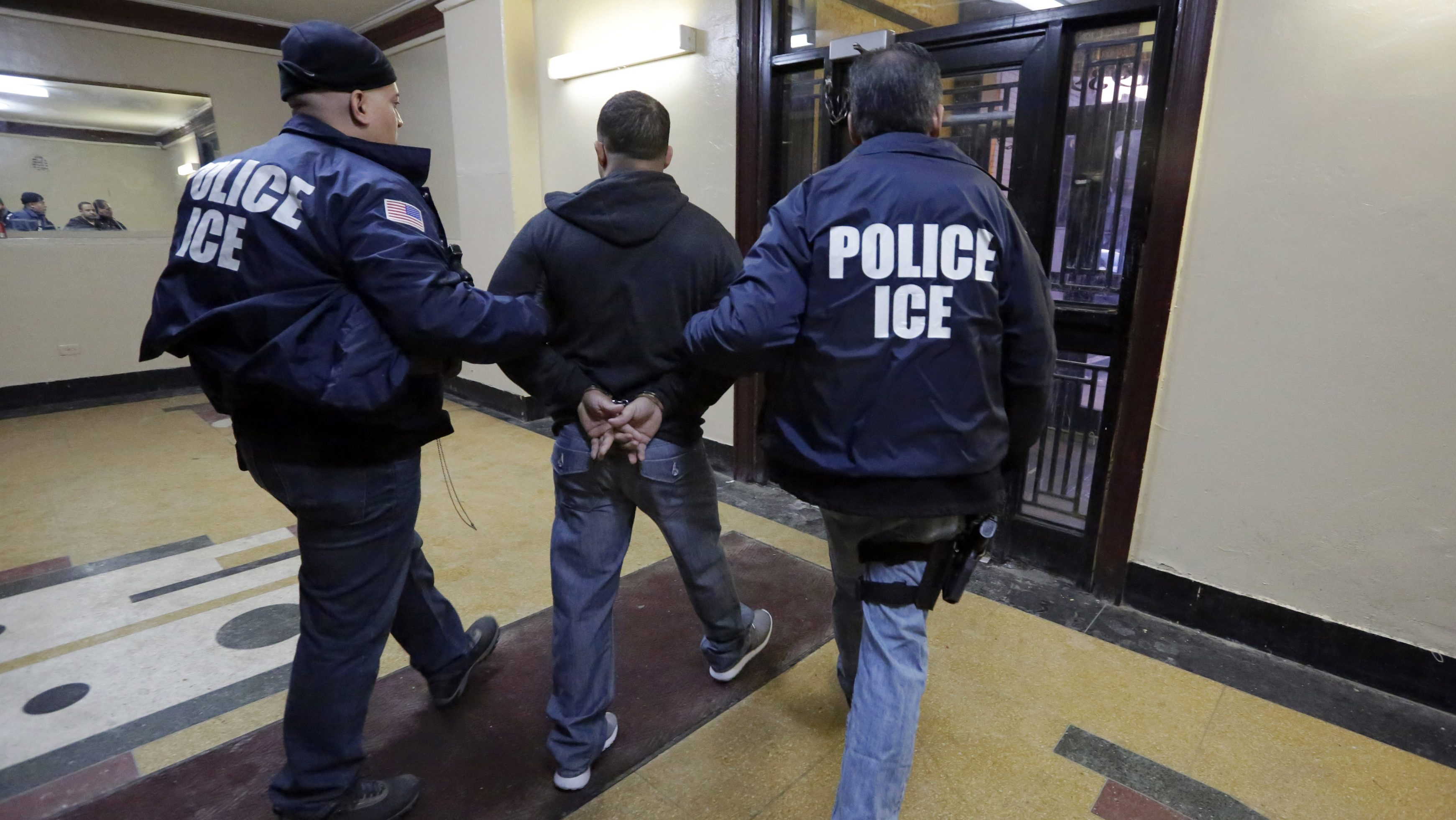 Immigration and Customs Enforcement officers escort an arrestee