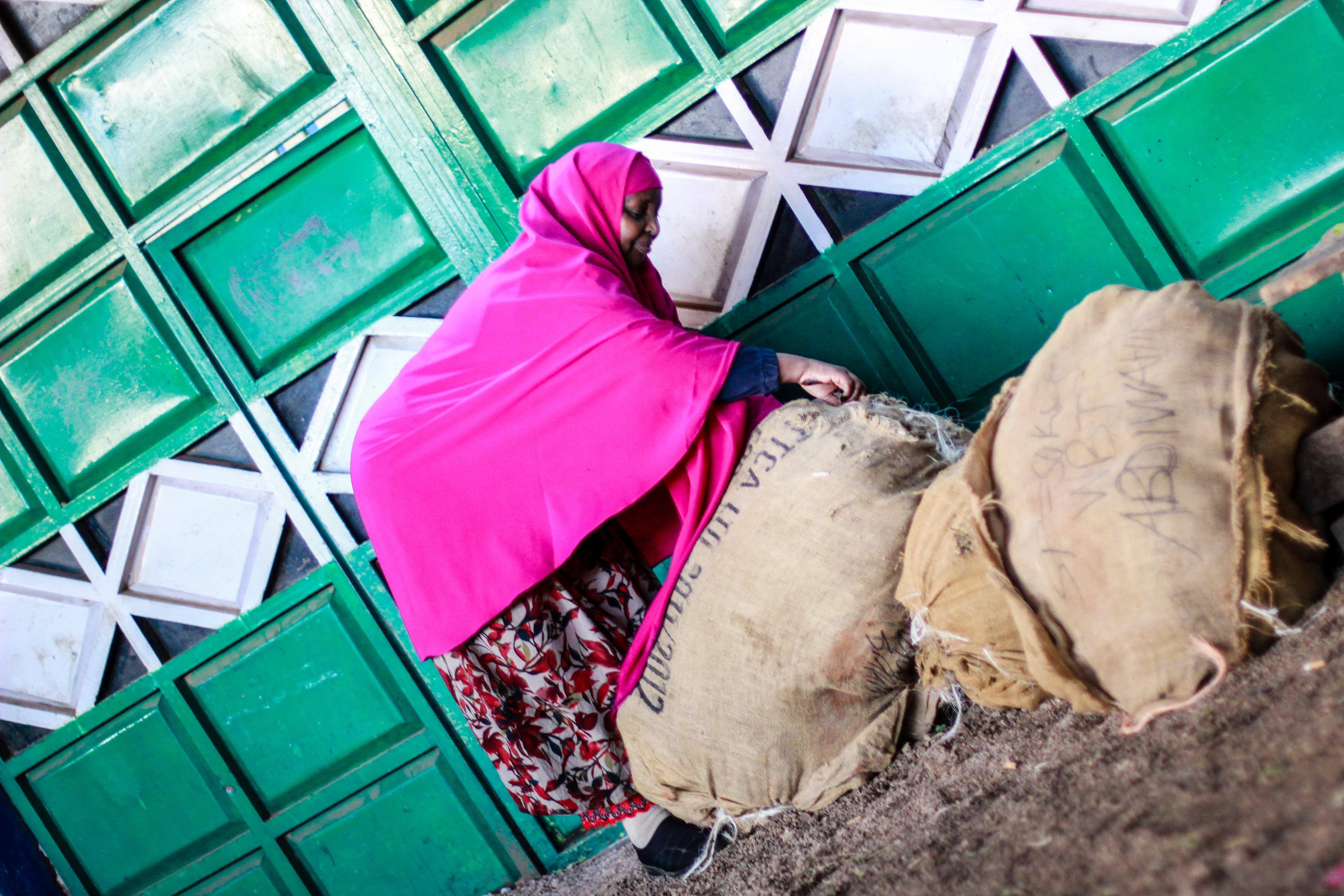 Ardo Omaar, a trader, inspects the sacks full of khat.