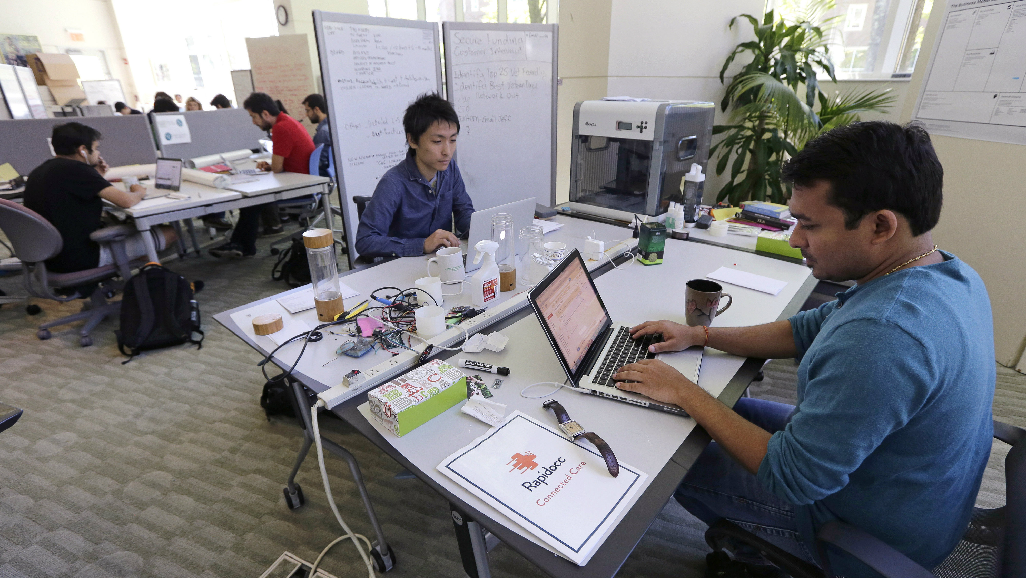 In this Thursday, June 30, 2016 photo, Babson College graduate school alumnus Abhinav Sureka, of Mumbai, India, right, types in his work space at the college in Wellesley, Mass. Some U.S. colleges are starting programs to help their alumni get visas through what critics say is a legal loophole. Foreign grads who want to stay and start a business typically apply for one of the 85,000 H-1B visas that the U.S. gives out each year. But college employees are exempt from that cap, so schools like UMass, Babson and CUNY have launched programs to hire alumni and foreign entrepreneurs and help them grow their businesses here.