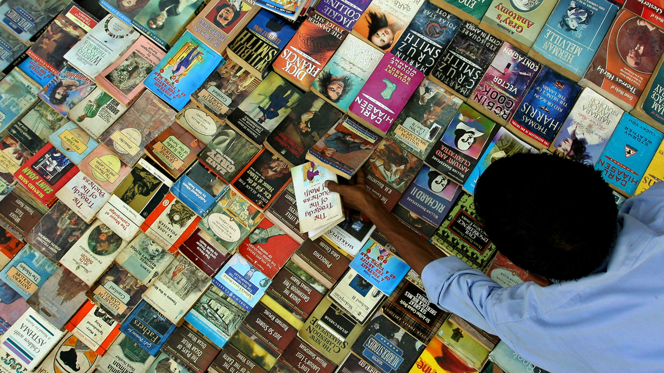 A vendor arranges books by the roadside in the old quarters of Delhi August 20, 2006.