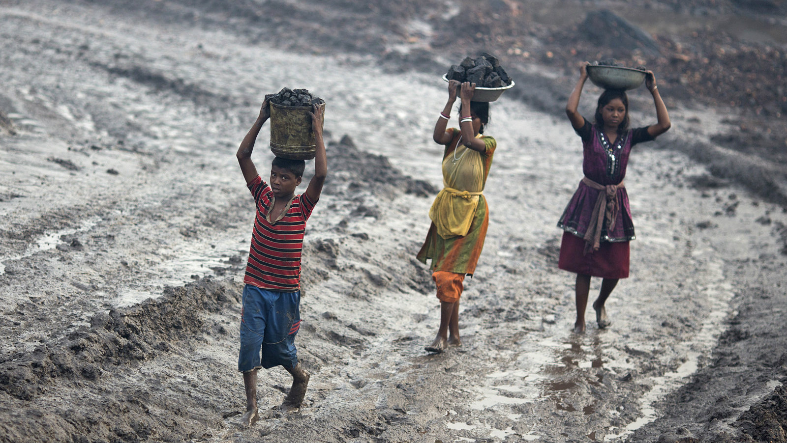 Locals carry coal from an open cast coal field at Dhanbad district in the eastern Indian state of Jharkhand September 20, 2012. With oil and gas output disappointing and hydropower at full throttle, Asia's third-largest economy still relies on coal for most of its vast energy needs. About 75 percent of India's coal demand is met by domestic production and, according to government plans, that won't change over the next five years. Picture taken September 20, 2012. To match INDIA-COAL/