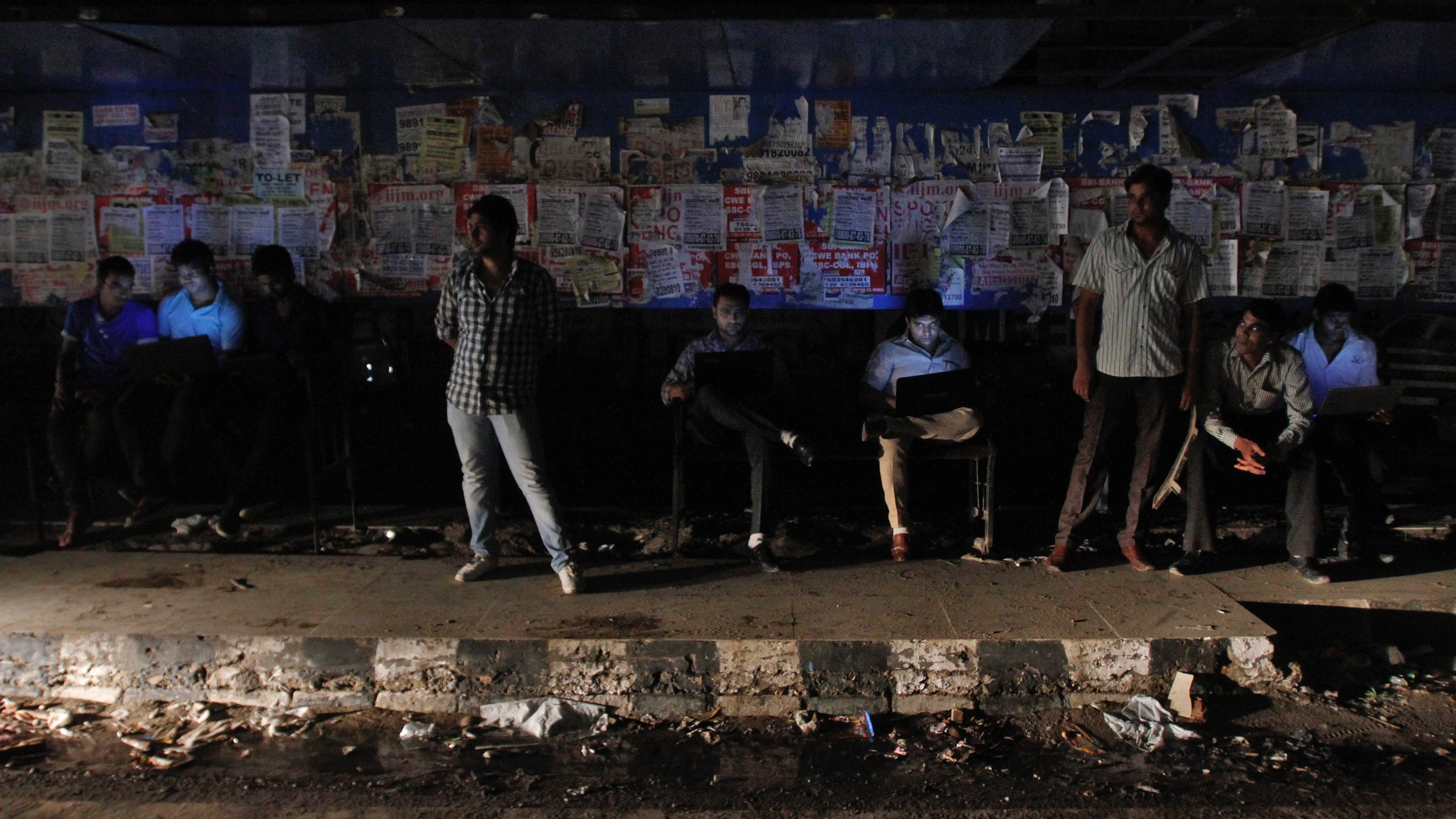 Commuters work on their laptops as they wait for the bus to arrive at a bus-stop during a power-cut at Noida