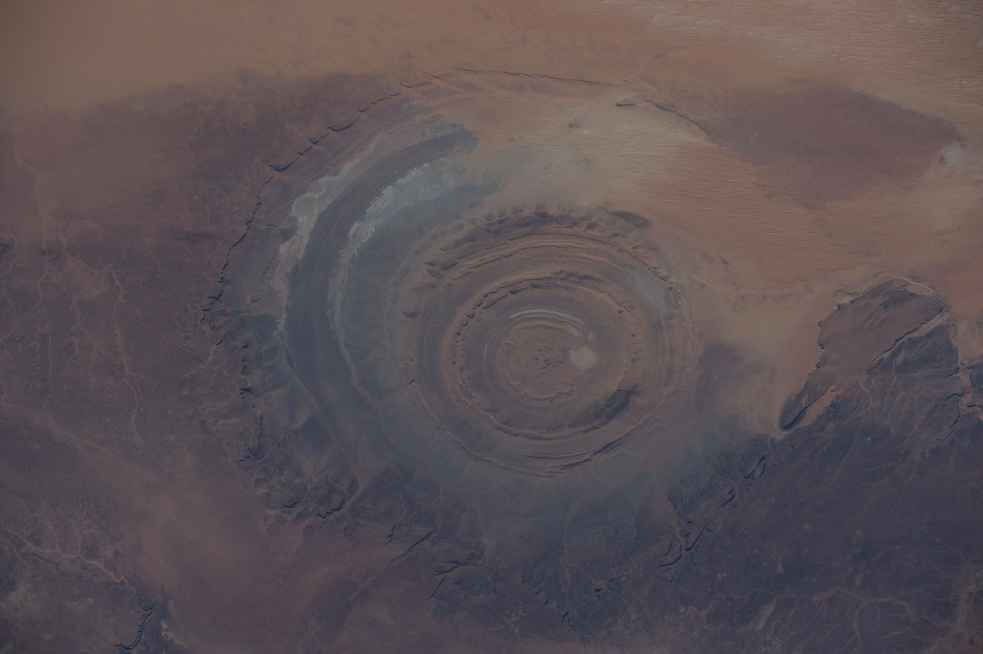 "The ancient Richat Structure in northwestern Mauritania, also known as the ""Eye of the Sahara"" was captured by astronauts aboard the International Space Station in 2014. It is a nearly perfect circle, and scientists are unclear whether it was formed by an underground volcano or a meteor impact."